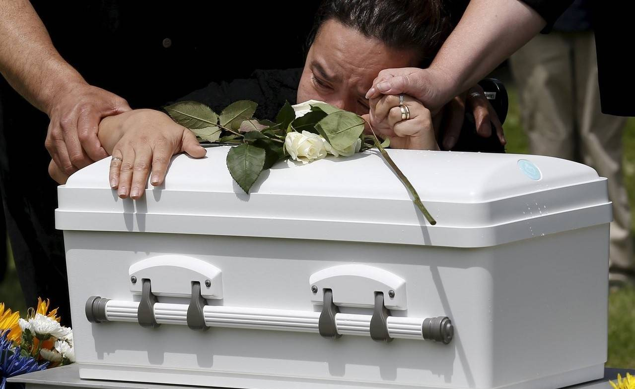 The grandmother of Angel Antonio cries on his casket.