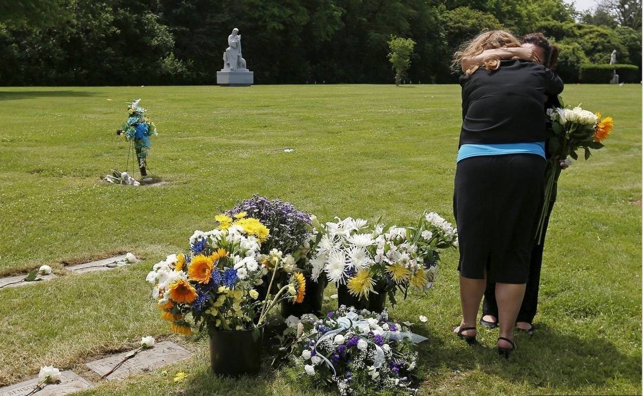 Rest in His Arms founder Susan Walker, left, comforts the grandmother of an abandoned newborn boy at a burial service at All Saints Cemetery in Des Plaines.