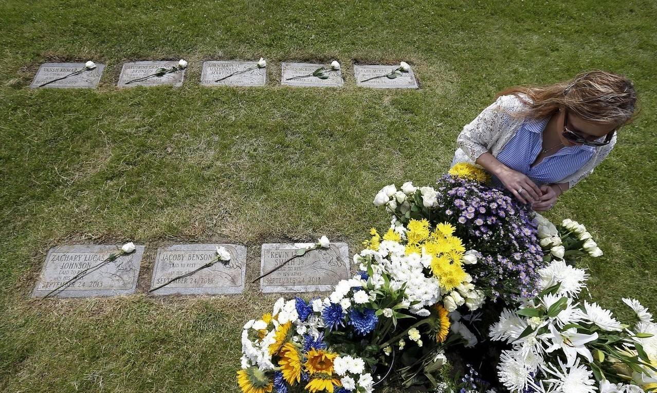 Suzy Matusiewicz sits beside the flowers covering the grave of an abandoned newborn baby boy during a burial service at All Saints Cemetery in Des Plaines.