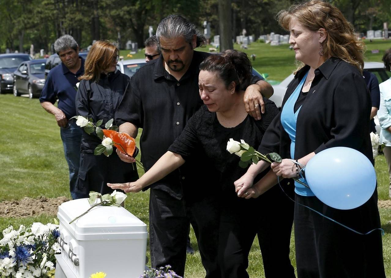 Rest in His Arms founder Susan Walker, right, helps the grandparents of an abandoned newborn boy visit his casket during a burial service at All Saints Cemetery in Des Plaines.