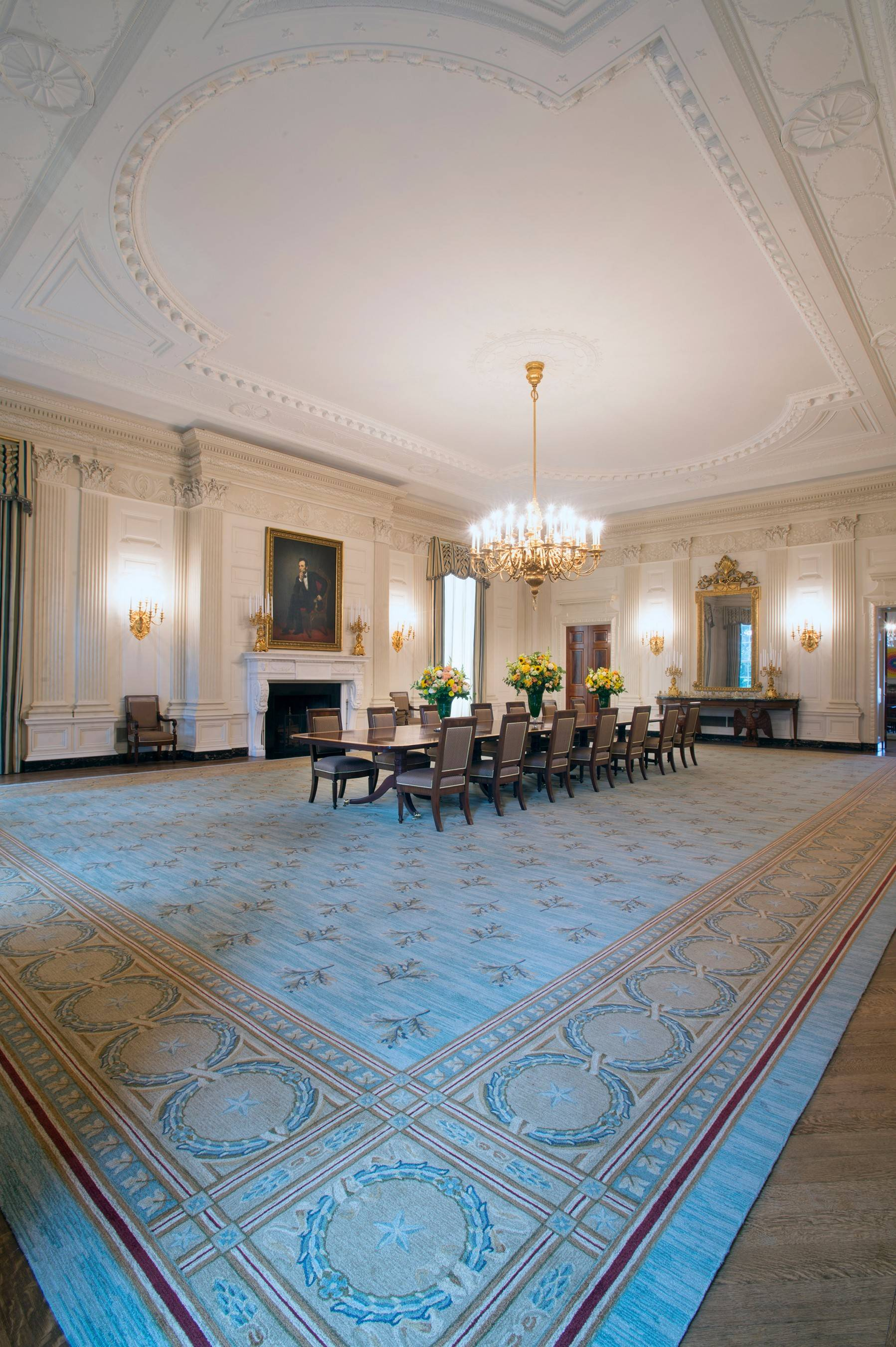 The State Dining Room of the White House in Washington, D.C., has a fancy new rug, custom-woven with motifs of wreaths and oak leaves taken from the intricate ornamental plasterwork of the ceiling.