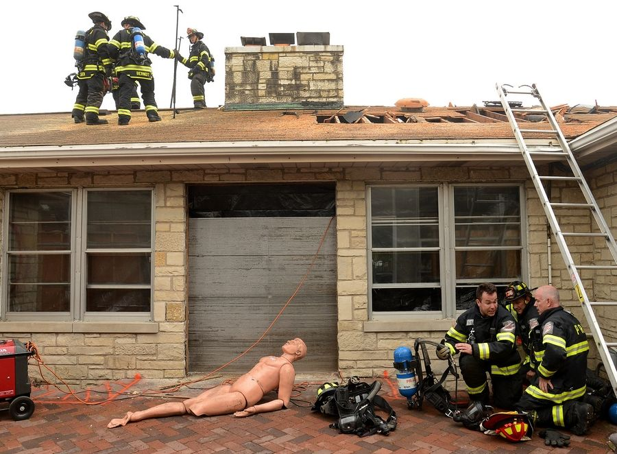 Firefighters from Des Plaines on the roof and those from Park Ridge on the ground conduct training exercises Thursday at the former Lurvey garden center building.
