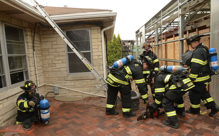 Park Ridge firefighter Chris Cleary crawls out of a basement window well while Des Plaines firefighters prepare to go on the roof of a 1950s ranch house most recently used as a garden center, but now set for demolition.