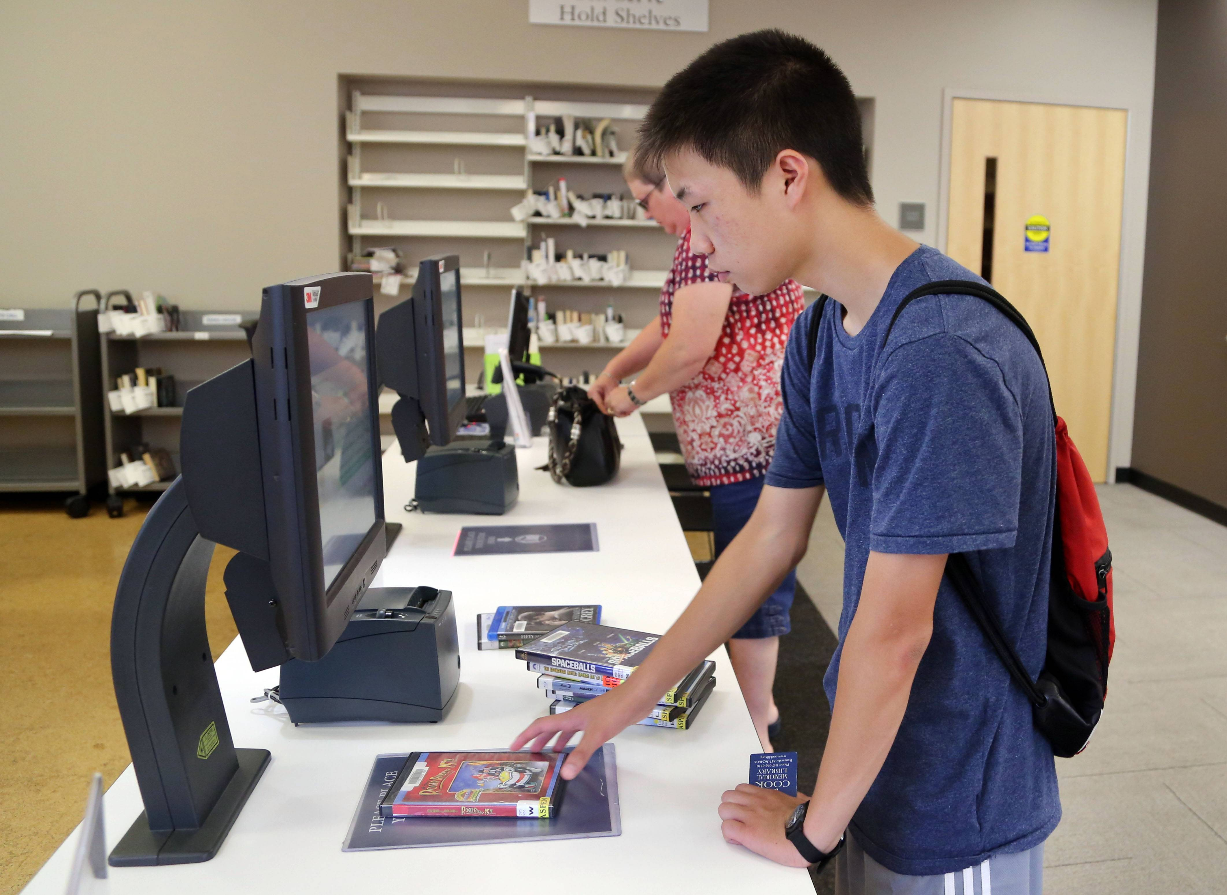 Matthew Huh, 14, of Vernon Hills checks out materials at the Aspen Drive Library.