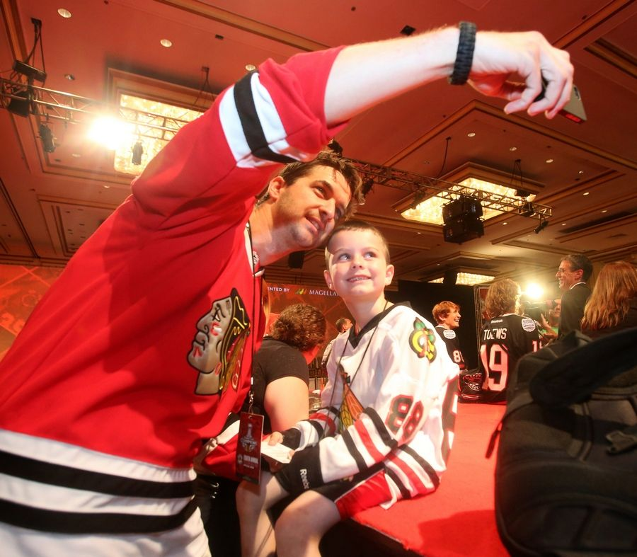Steve Bozue and his son Steve Bozue, 7, of Yorkville take a photo during the 8th annual Blackhawks Convention at the Hilton Chicago.