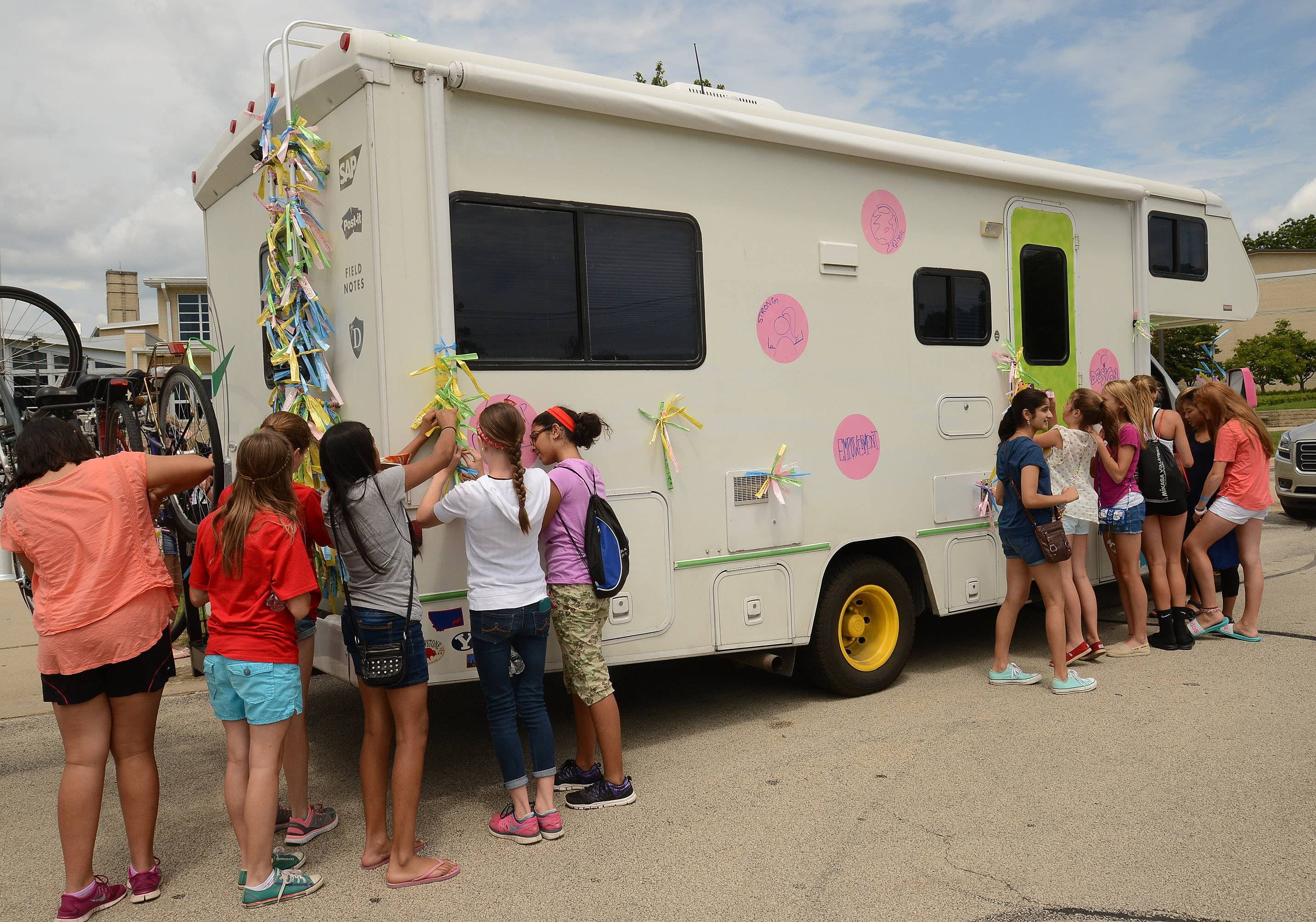 Bob Chwedyk/bchwedyk@dailyherald.comBarrington Middle School 7th and 8th grade girls attached ribbons to the RV driven by Girls Driving for a Difference after attending a leadership workshop at Barrington High School Monday.