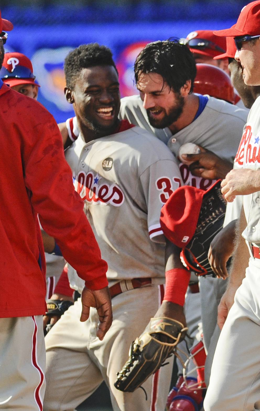 Philadelphia Phillies pitcher Cole Hamels, second from right, hugs center fielder Odubel Herrera after pitching a no-hitter against the Chicago Cubs in Chicago, Saturday, July 25, 2015. Herrera caught a fly ball hit by Cubs' Kris Bryant to end the game. The Phillies won 5-0.