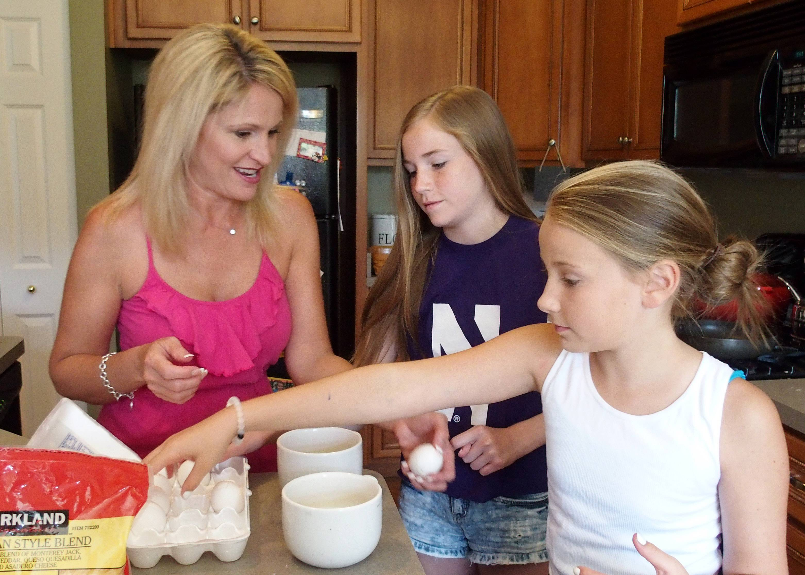 Noting that everyone helps out, Dolly McCarthy hands the scrambled egg duties at breakfast to daughters, Caitlin, center, and Molly.