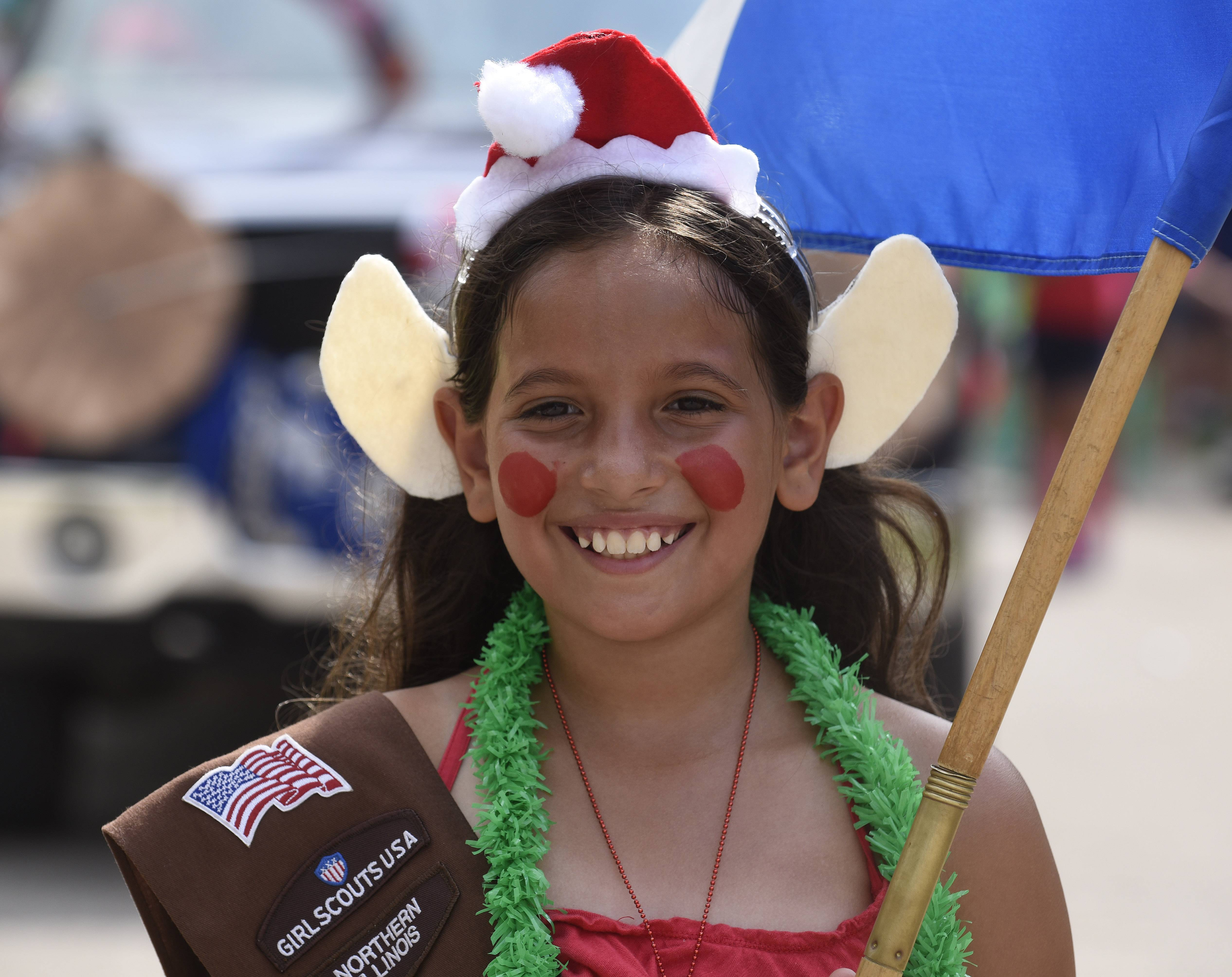 Francesca Bove, 9, of Hanover Park dons her Santa hat and elf ears as she and the rest of her fellow Girl Scouts march in the Streamwood Summer Celebration parade on Saturday.