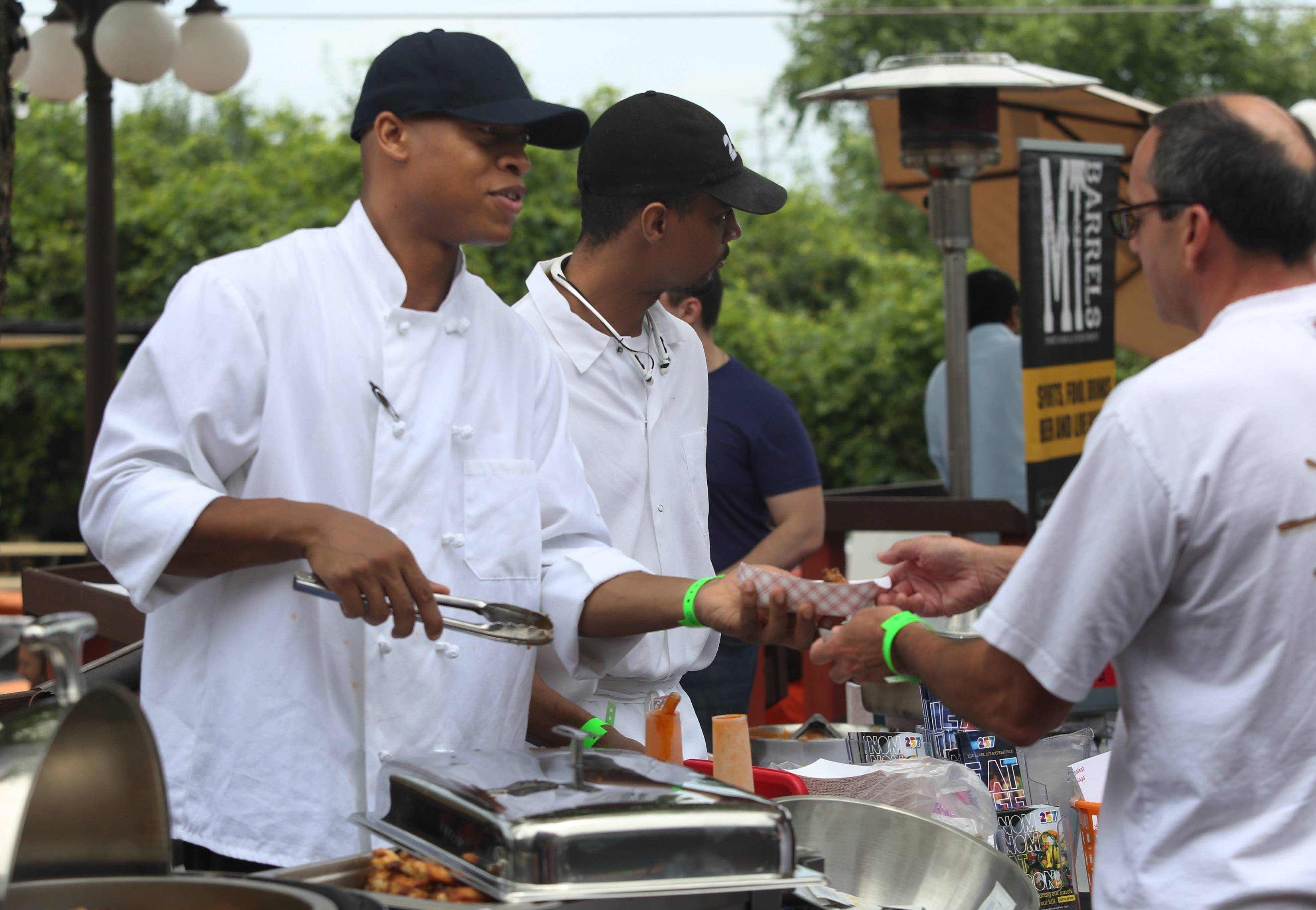 Banquet chef Arnold Ivey, left, and cook Kirk Wilborn of Level 257 serve wings to customers during the Woodfield Area Children's Organization Wingfest and Bags Tournament Sunday at Drink in Schaumburg.
