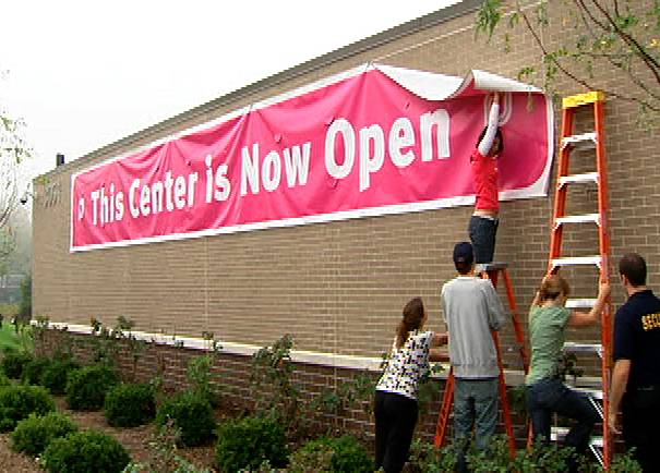 "Workers raise the ""open"" sign at the Planned Parenthood clinic in Aurora in 2007."