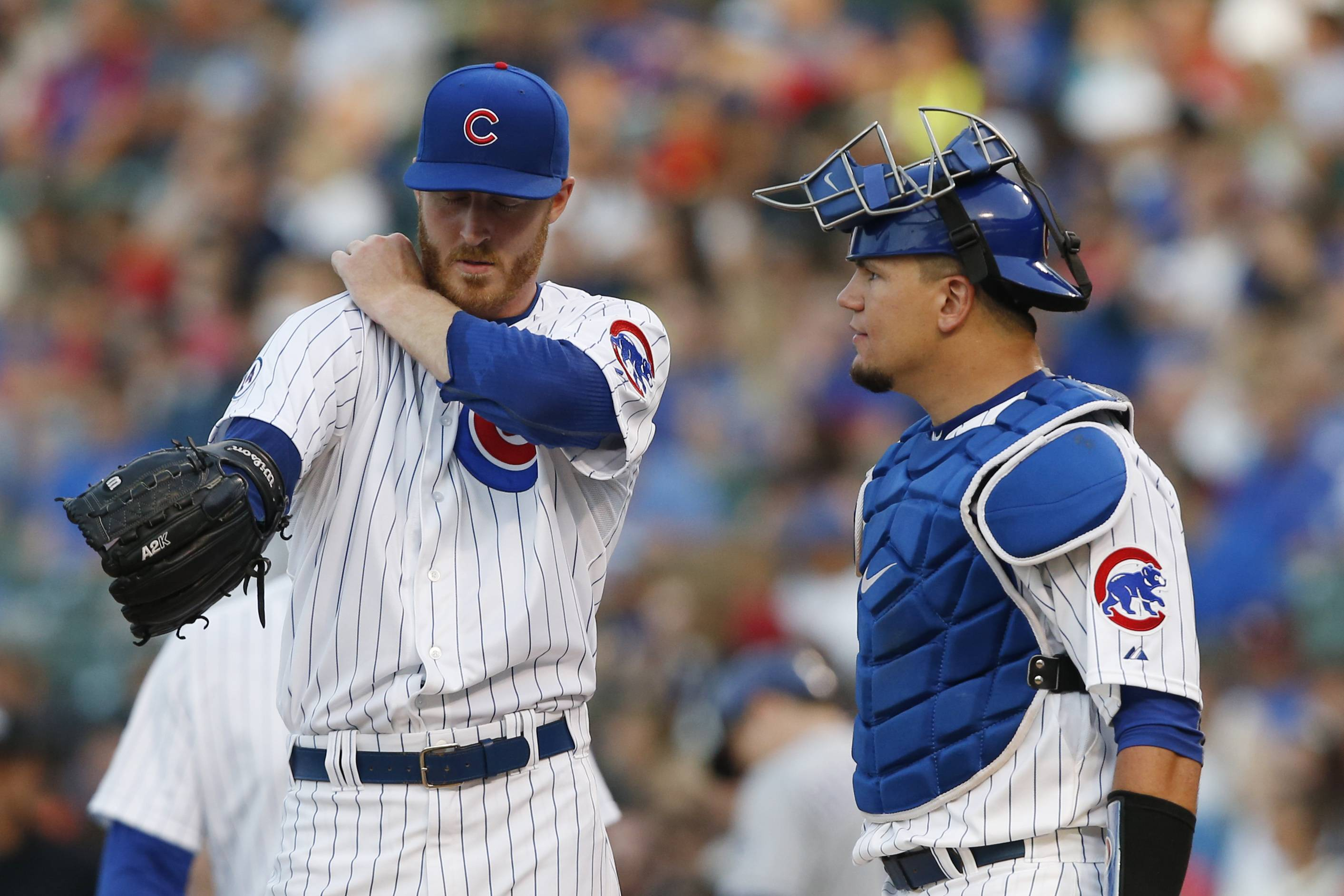 Chicago Cubs starting pitcher Dallas Beeler and catcher Kyle Schwarber confer during the first inning of a baseball game against the Colorado Rockies in Chicago, Tuesday, July 28, 2015.