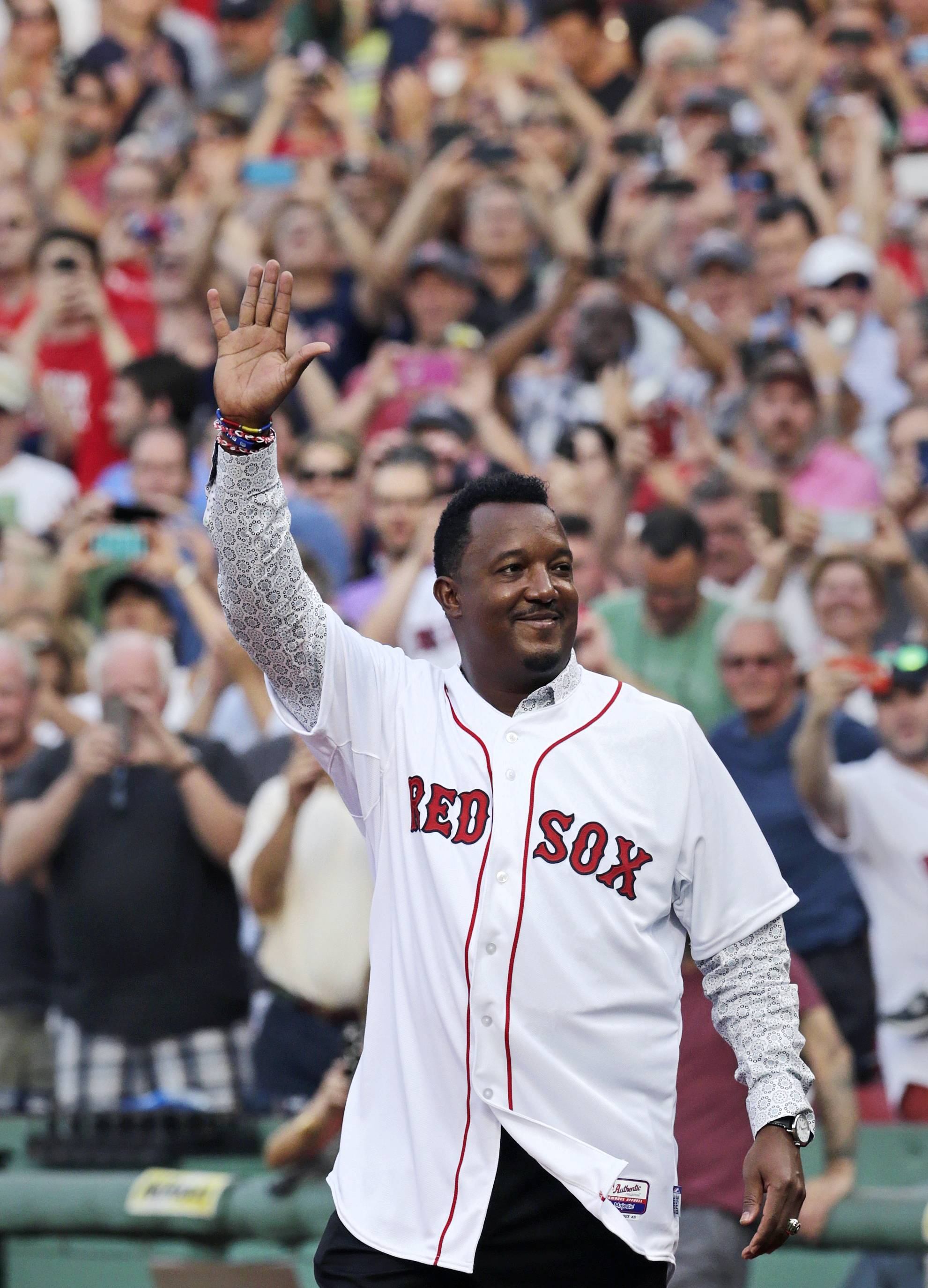 Baseball Hall of Fame member and former Boston Red Sox player Pedro Martinez acknowledges fans during a ceremony where his jersey was retired prior to a baseball game against the Chicago White Sox at Fenway Park in Boston, Tuesday, July 28, 2015.