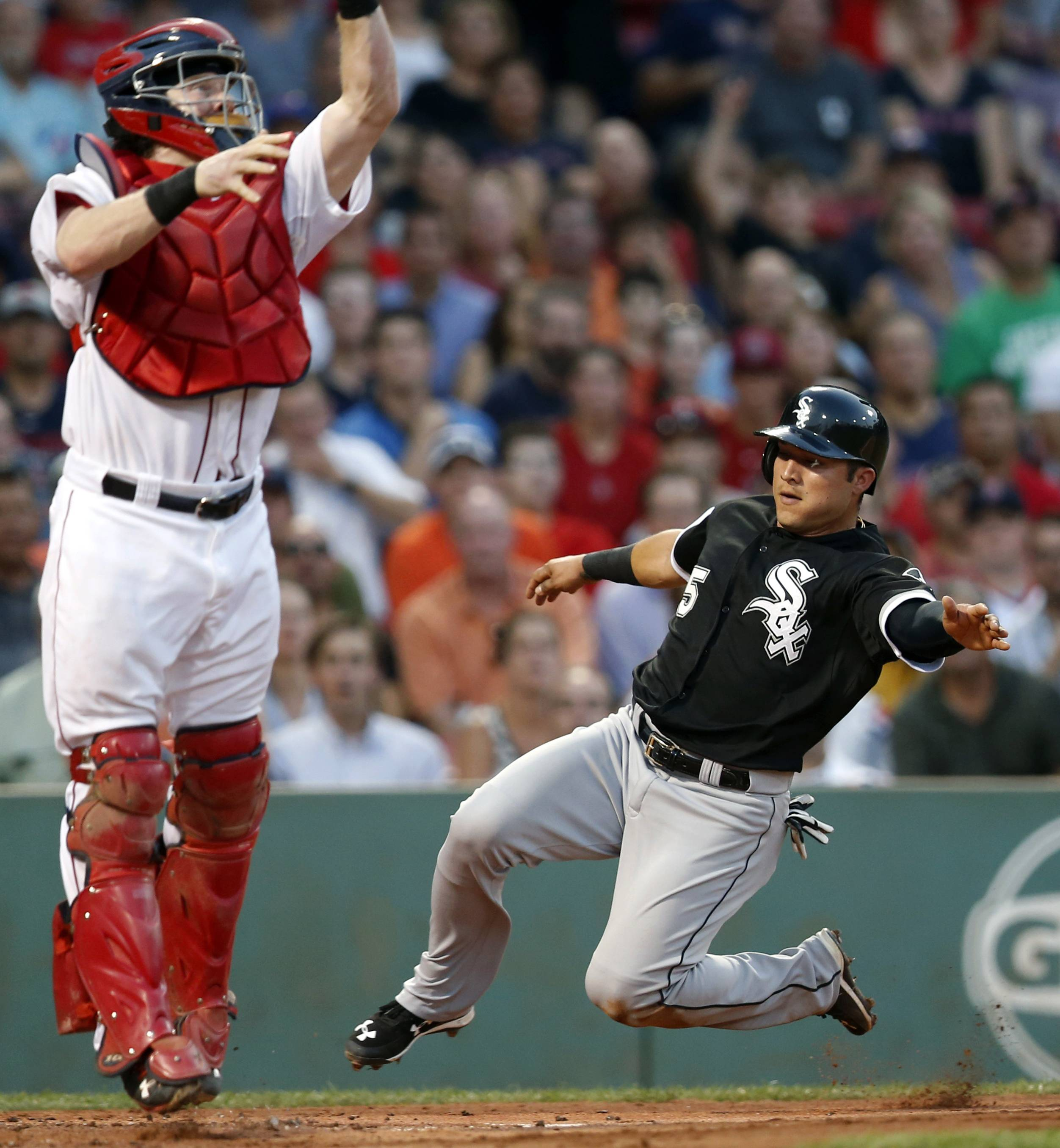 Chicago White Sox's Carlos Sanchez (5) scores on a single by Adam Eaton as Boston Red Sox's Ryan Hanigan jumps for the high throw during the second inning of a baseball game in Boston, Wednesday, July 29, 2015.