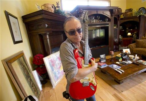 In this, Wednesday, July 22, 2015 photo, 1970�€™s heartthrob David Cassidy holds one of his favorite guitars as he gives a tour of his five-bedroom Florida mansion in Fort Lauderdale, Fla. Cassidy, 65, is auctioning the waterfront home and all its furnishings Sept. 9 as part of bankruptcy and divorce proceedings. The pianos and guitars displayed throughout his home won�€™t be included in the auction, as he�€™s working on a Christmas album and an album of songs he learned from his father, actor and singer Jack Cassidy. (AP Photo/Wilfredo Lee)
