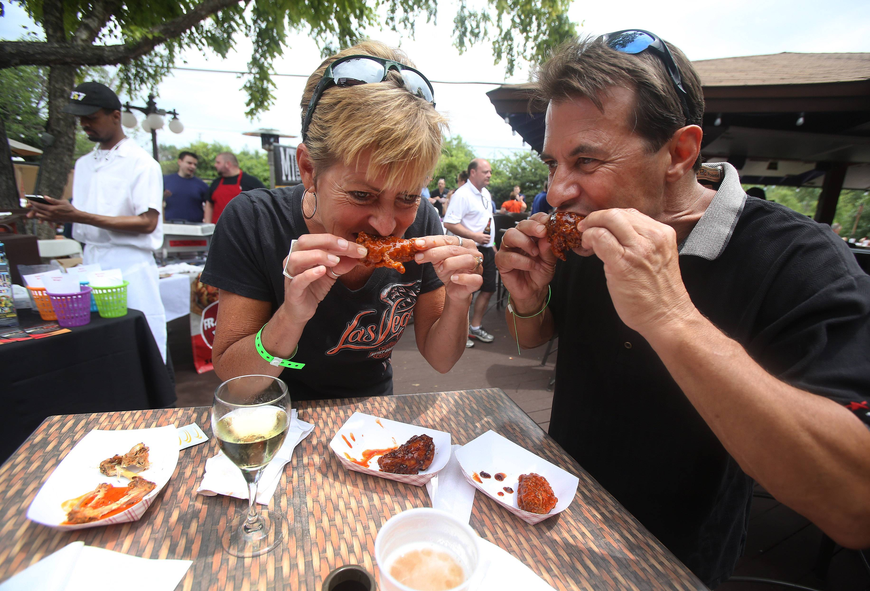 "Lynn and Pete Manhard of Vernon Hills eat the award-winning wings made by Frato's Pizza during the Woodfield Area Children's Organization Wingfest and Bags Tournament last Sunday at Drink in Schaumburg. After winning the ""Best in the 'Burbs"" honor, the Schaumburg pizzeria donated its $250 cash prize back to the charity."
