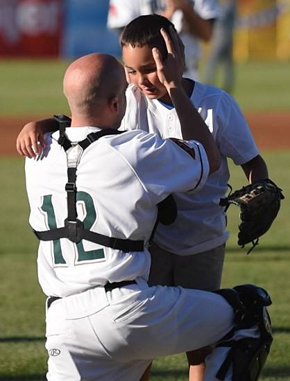 Air Force Technical Sgt. Joe Amore of Geneva greets his son, Anthony, 8, after surprising him by catching his ceremonial first pitch Friday at the Kane County Cougars game Friday. Amore, a 1997 graduate of Geneva High School, returned this week from a six-month tour in Kuwait.