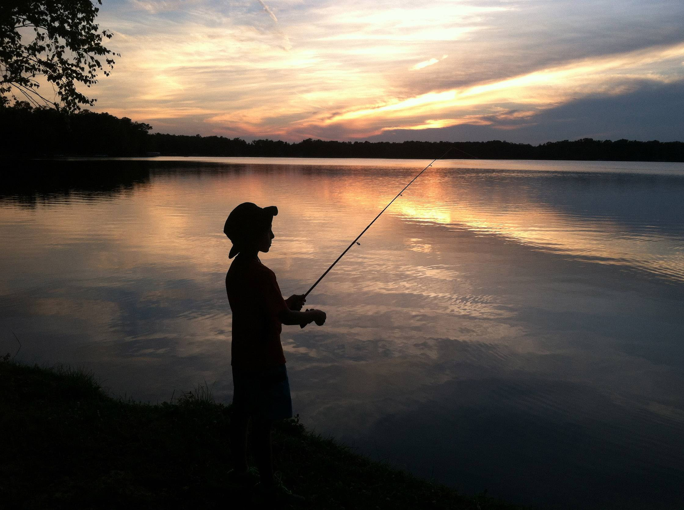 A boy fishes on Legend Lake as the sun sets in Wisconsin.