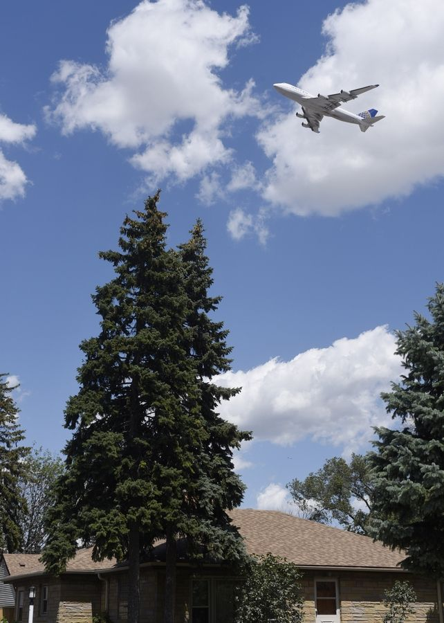 A plane climbs above the Hillside Drive neighborhood in Bensenville after taking off Friday from O'Hare International Airport in Chicago.