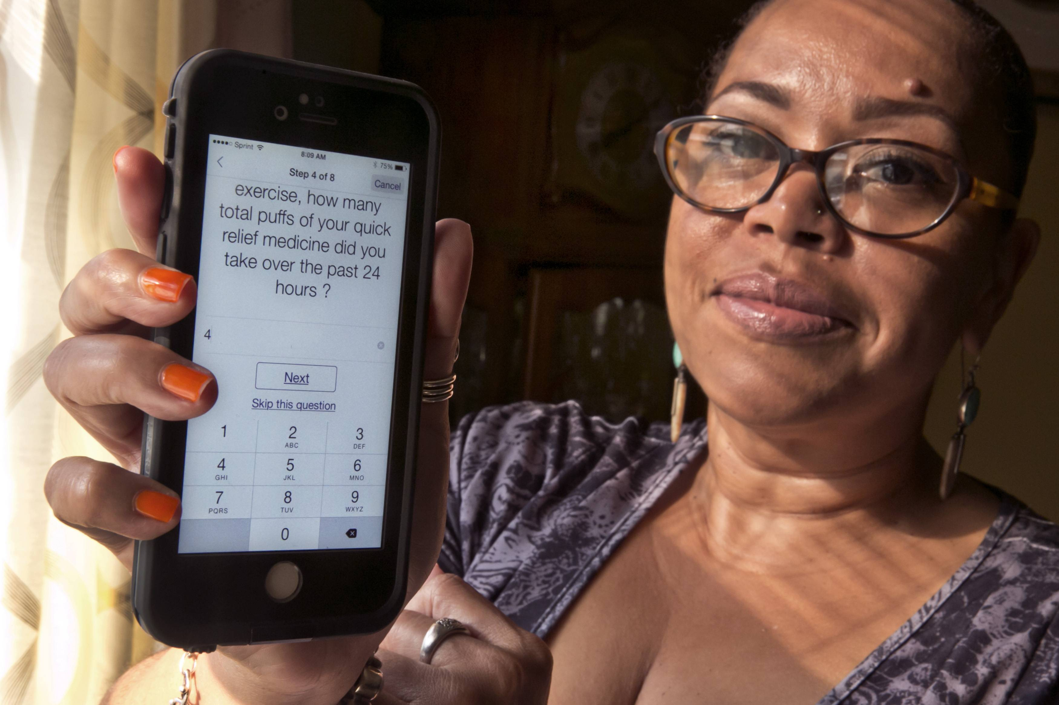 Asthma sufferer Elizabeth Ortiz, who uses the Asthma Health smartphone app daily to track her condition, measures her lung power each day by breathing into an inexpensive plastic device and then typing the results into the app, which also asks if she's had difficulty breathing or sleeping, or taken medication that day.