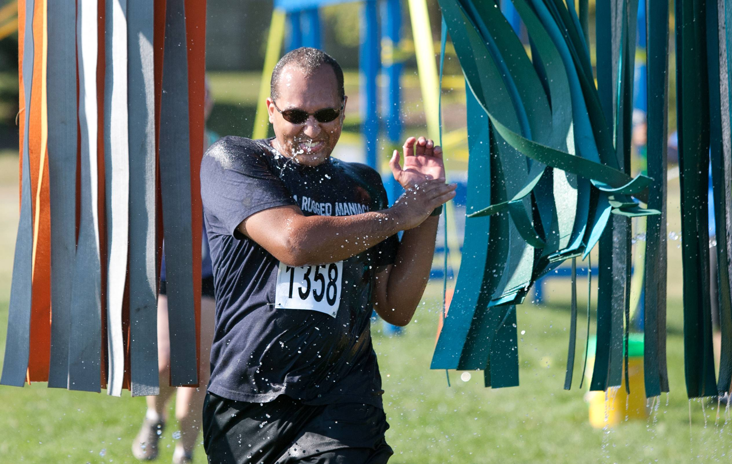 Jason Williams of Palatine runs through the car wash portion of the second annual Varsity Rush obstacle race Saturday at Frontier Park in Naperville.