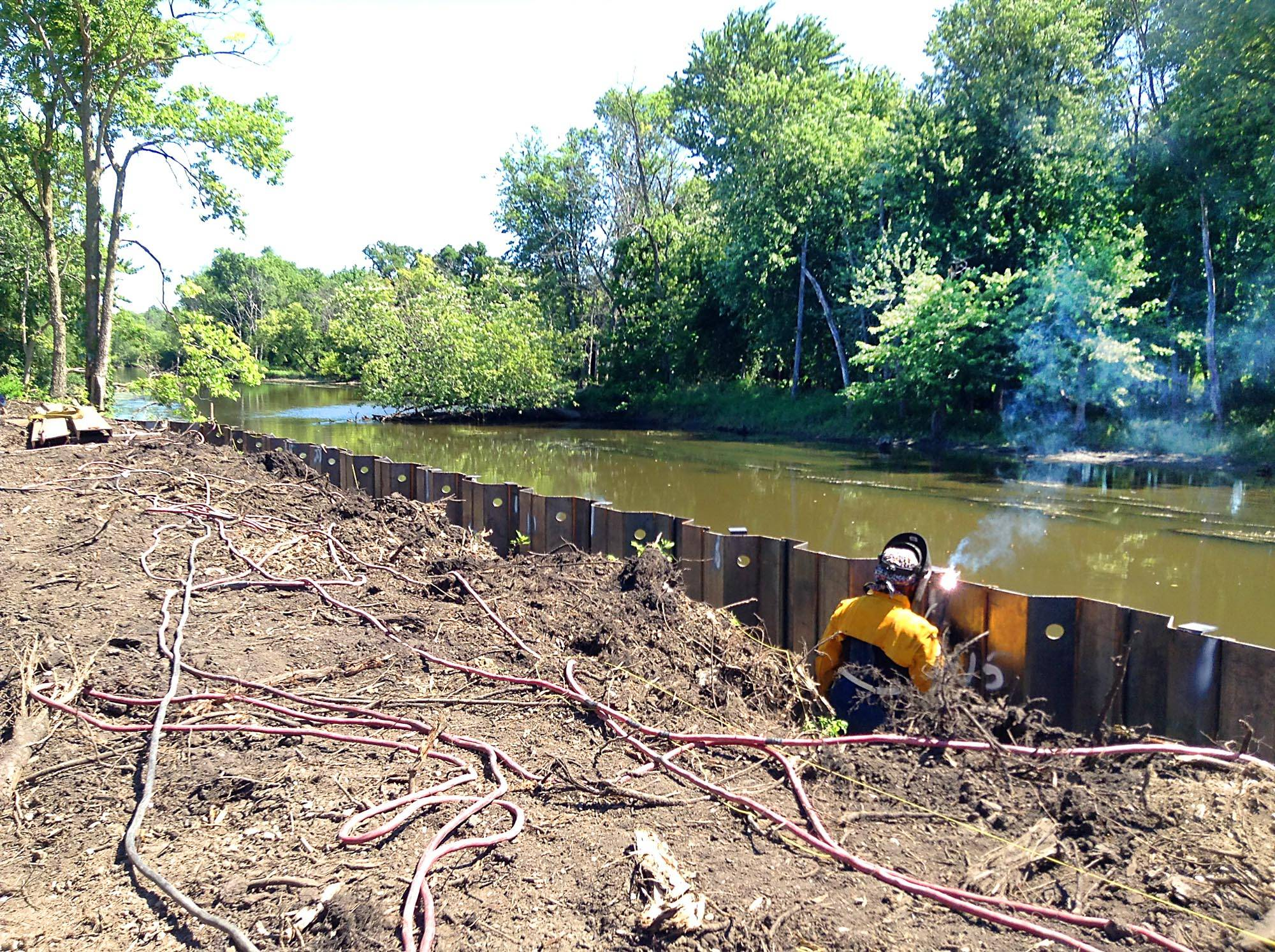 A welder works on a retaining wall as part of a project to close the last gap on the Des Plaines River Trail.