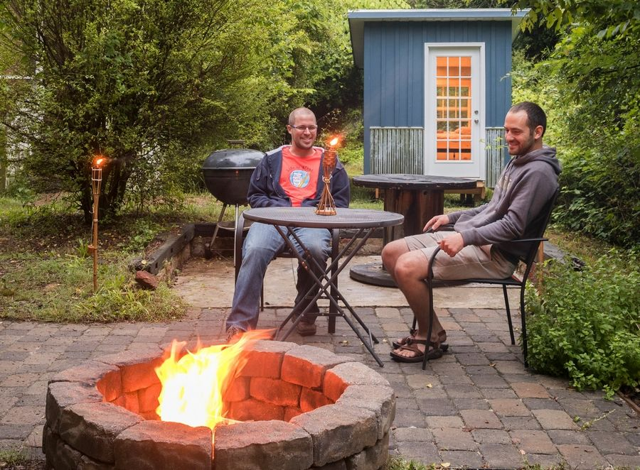 Kevin Riedel, right, often entertains friends around his fire pit.