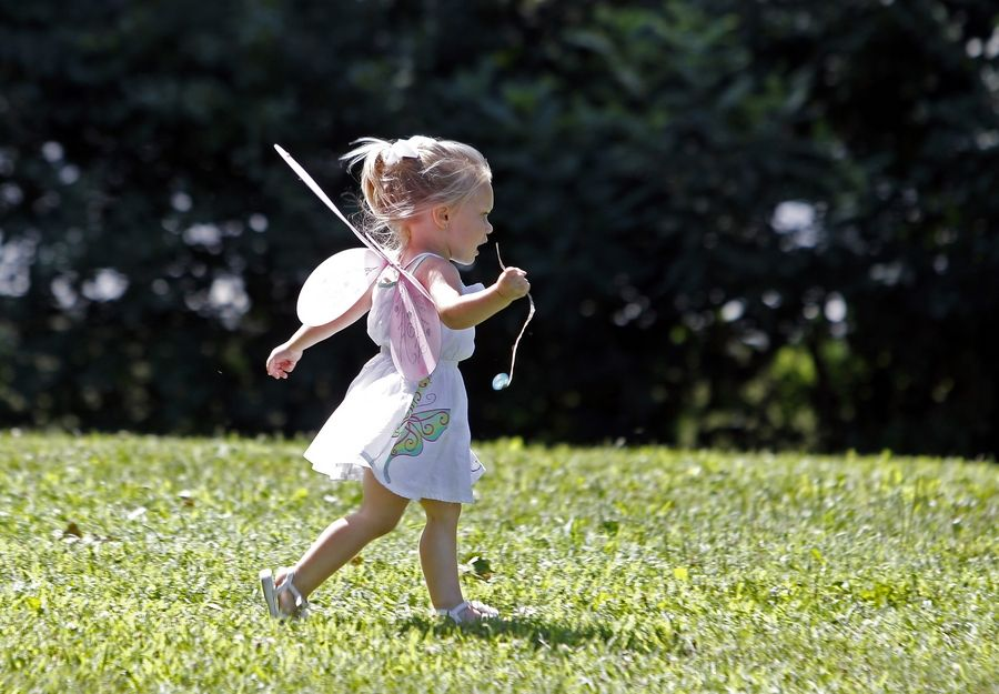 Dressed as a faerie, 2-year-old Annabelle Haiduke of Marseilles runs across a field Saturday during the 11th annual World of Faeries Festival at Vasa Park in South Elgin.