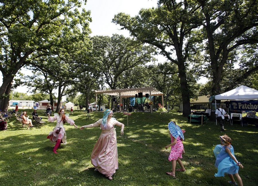 Faeries dance to the music during the 11th annual World of Faeries Festival Saturday at Vasa Park in South Elgin.