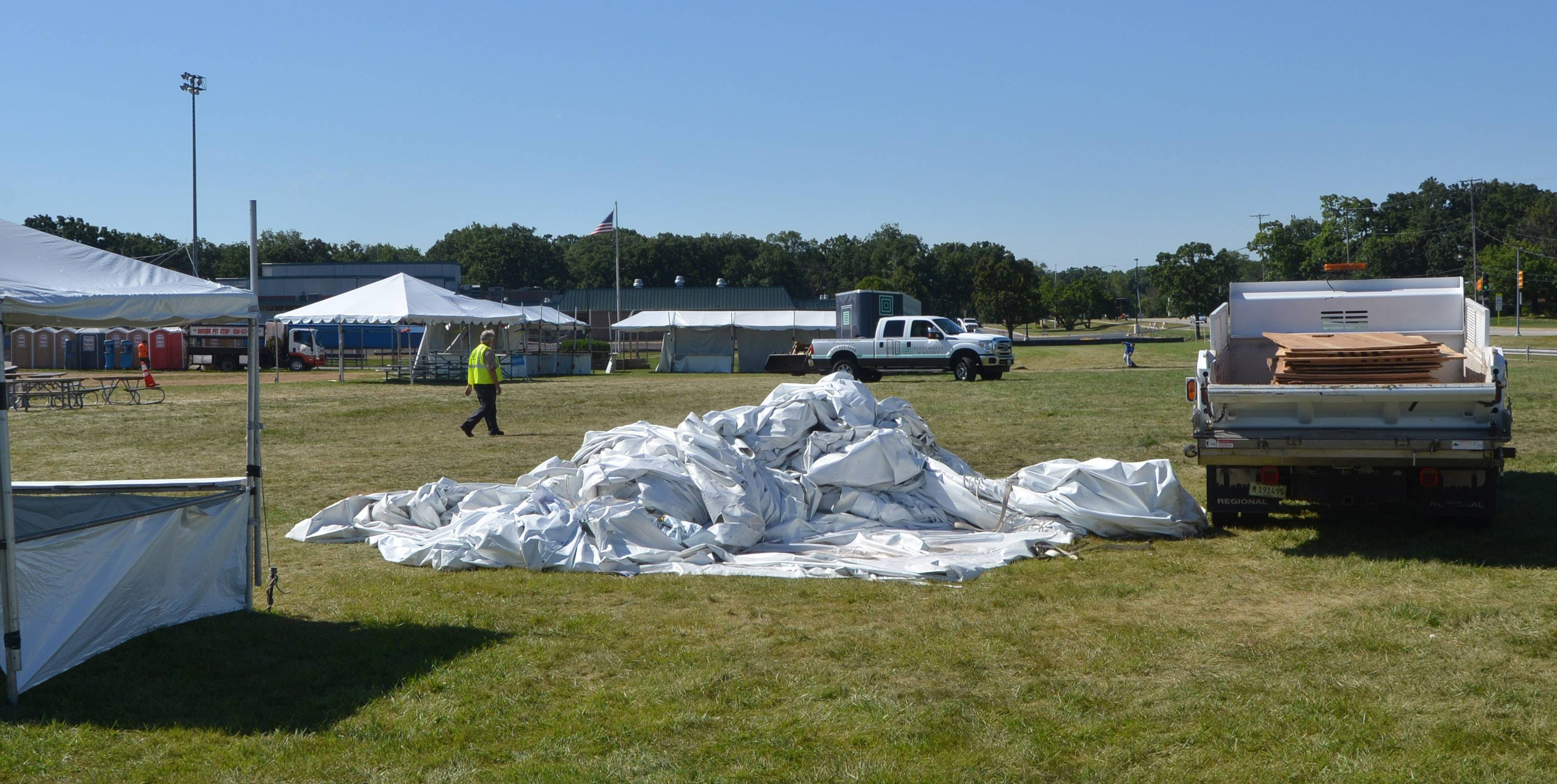 Crews work Monday to clean the site of Wood Dale's Prairie Fest where one person was killed and 22 were injured Sunday when a large gust of wind knocked down a tent where visitors had gone to seek shelter from a fast-moving storm.