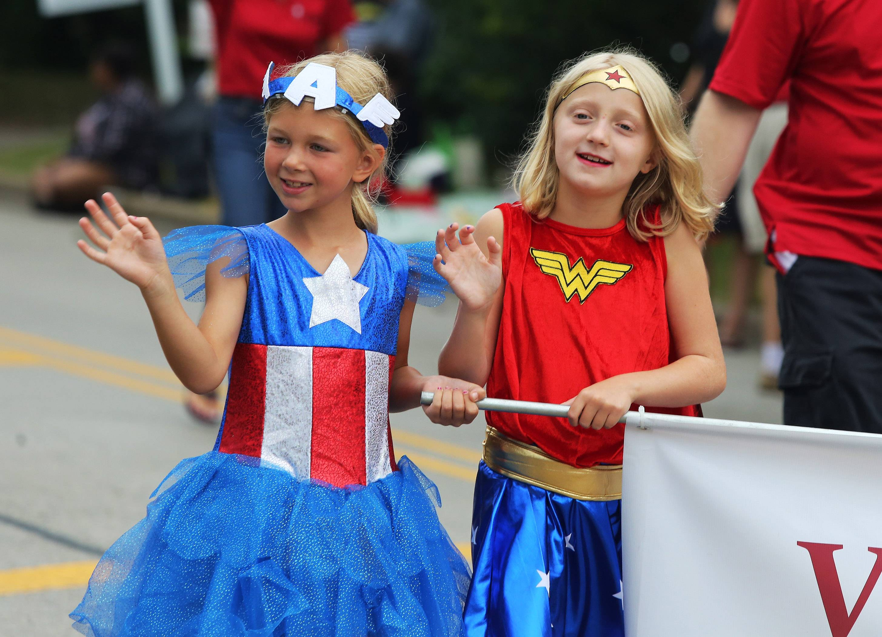 "Dressed as superheroes, Ruby Muetz, left, and Abi Harris of Gurnee march in the Gurnee Days Parade Sunday along Old Grand Avenue. The parade offered 71 entries whose theme was ""Gurnee Days Celebrates Heroes."""
