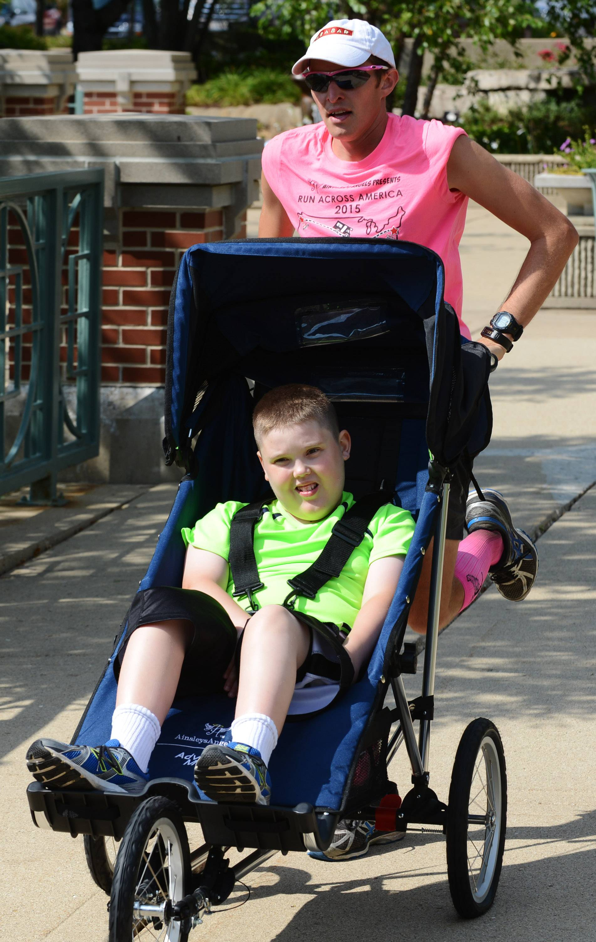 "Shaun Evans, pushes Alex Gorz, 12, of Midlothian, who has cerebral palsy and autism, on a trial spin in a running stroller, which he terms a ""freedom chariot."" Evans stopped in Schaumburg on Thursday during a 3,200-mile run across 15 states while pushing his 9-year old son Shamus, who has cerebral palsy, in a running stroller."