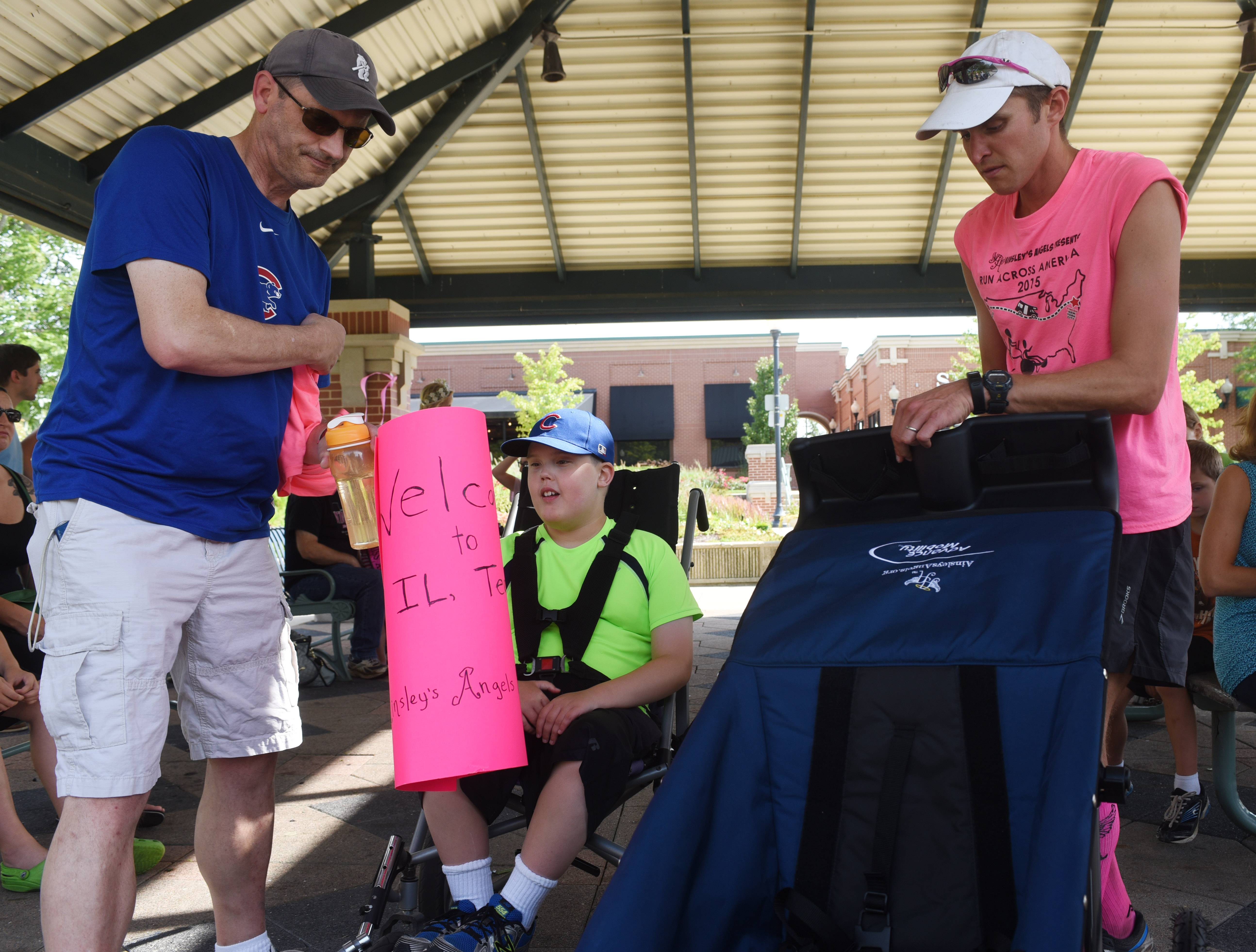 "Shaun Evans, right, presents Alex Gorz, 12, of Midlothian with a running stroller that he terms a ""freedom chariot"" in Schaumburg Thursday. Evans is running 3,200 miles across 15 states while pushing his 9-year old son Shamus, who has cerebral palsy, in a running stroller to raise awareness for Ainsley's Angels. At left is Tom Gorz, Alex's dad."