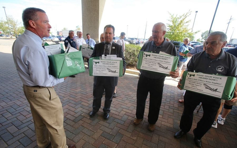 Elk Grove Village Mayor Craig Johnson, left, Itasca Village President Jeff Pruyn and other Elk Grove officials helped deliver a total of 16 boxes of comment cards about O'Hare noise to an FAA meeting Thursday at Belvidere Banquets in Elk Grove Village.