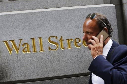 FILE - In this Monday, July 6, 2015, file photo, a man uses a mobile phone while walking by a building in the Financial District in New York. Slightly disappointing European growth figures, notably out of France and Italy, weighed on stock markets Friday, Aug. 14, 2015, while oil prices sank to their lowest level since early 2009. (AP Photo/Mark Lennihan, File)