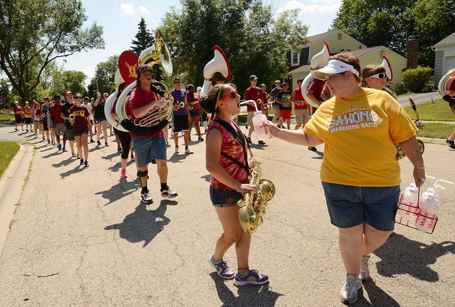 Volunteer Ronda Wilkes gives baritone saxophonist Myriam Brito a water break as the Schaumburg High School Band parades around the neighborhood getting ready for Septemberfest.