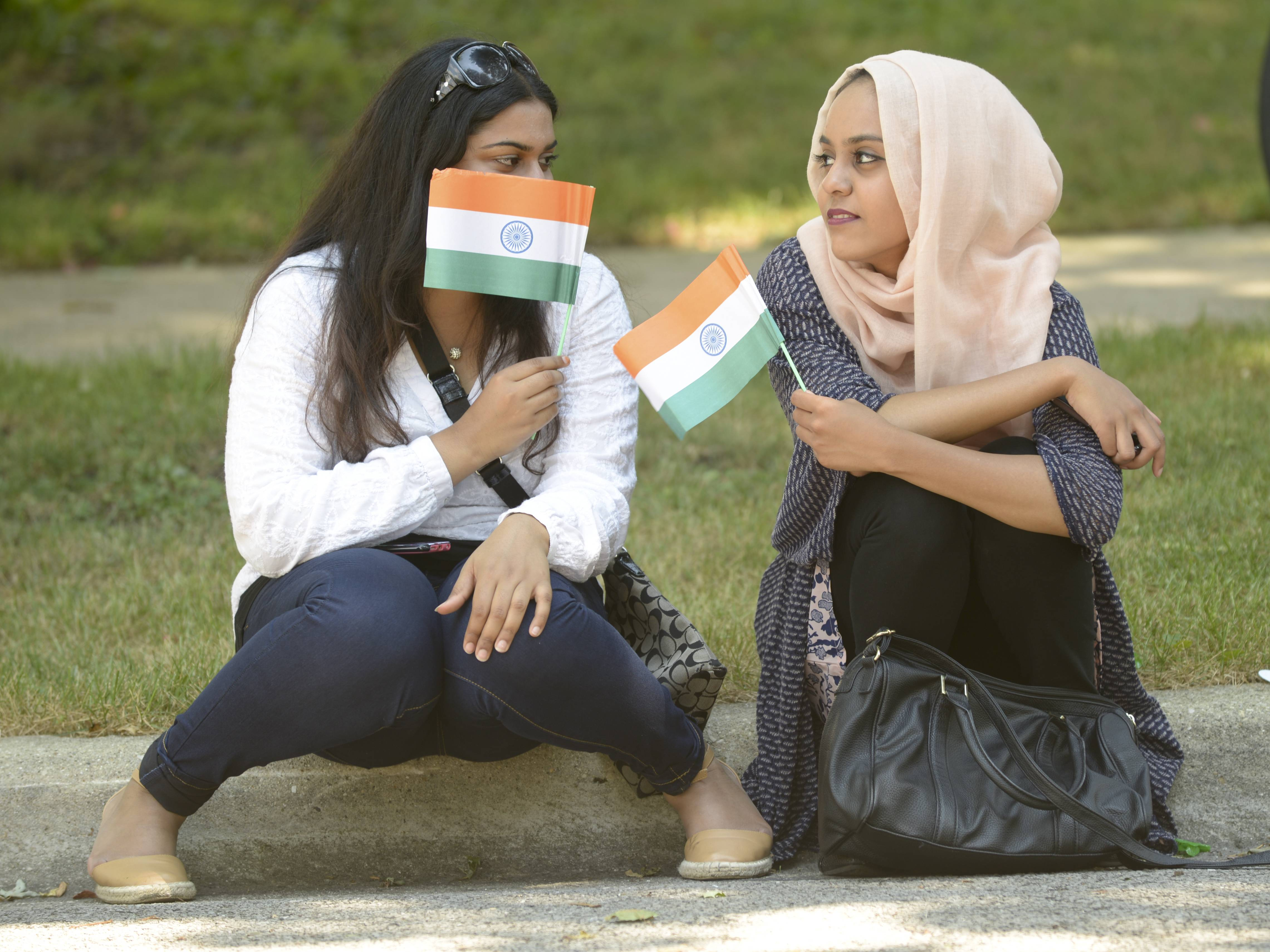 Anum Razak of Streamwood and Shajwa Hussain of Naperville watch the Naperville Indian Community Outreach's first India Day Parade on Sunday. The event, and a ceremony that followed, celebrated India's 69th year of independence.
