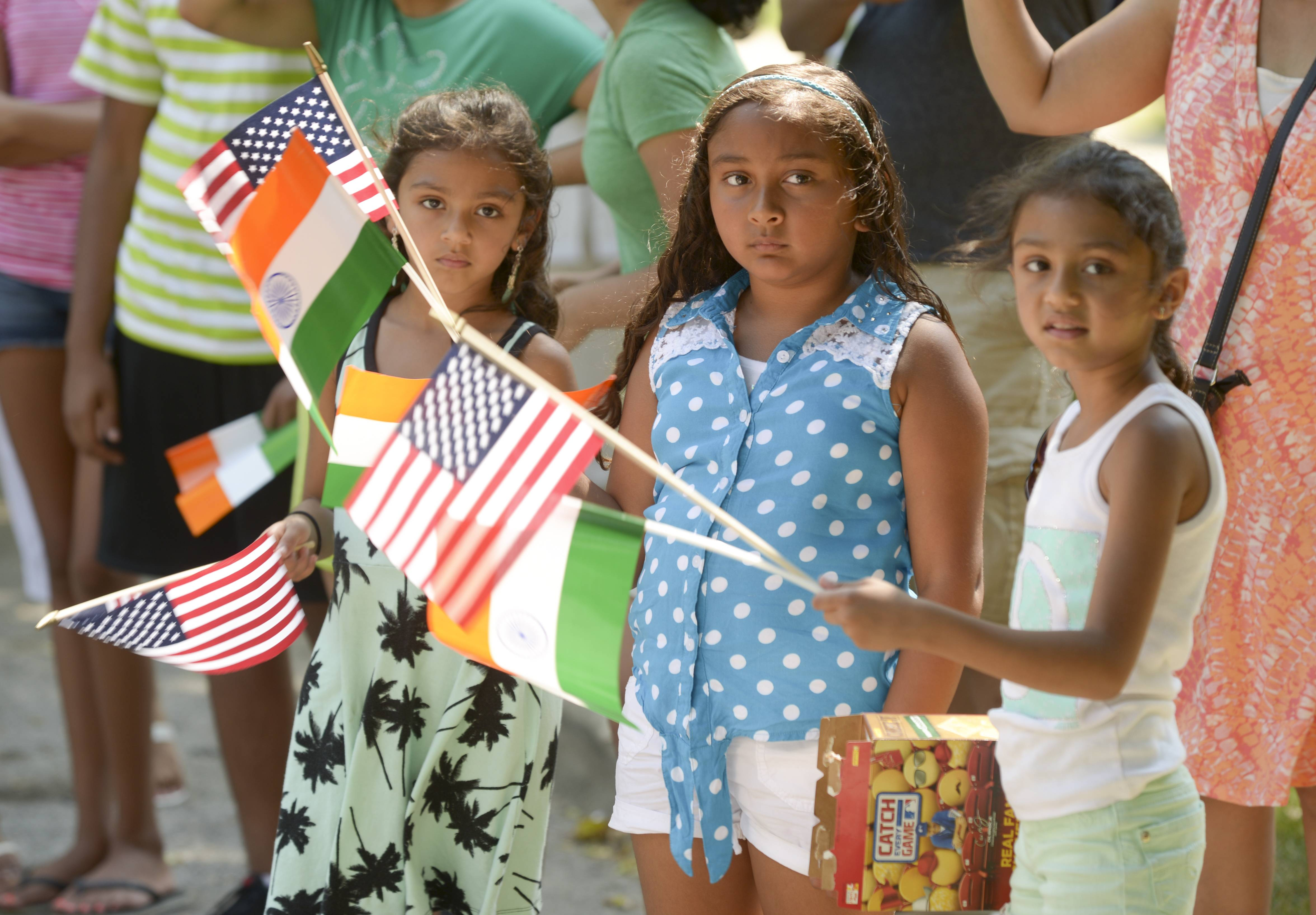 Cousins Jasmine, Siy and Jessica Shah of Naperville wave American and Indian flags Sunday while watching the Naperville Indian Community Outreach's first India Day Parade. The event marked India's independence day.