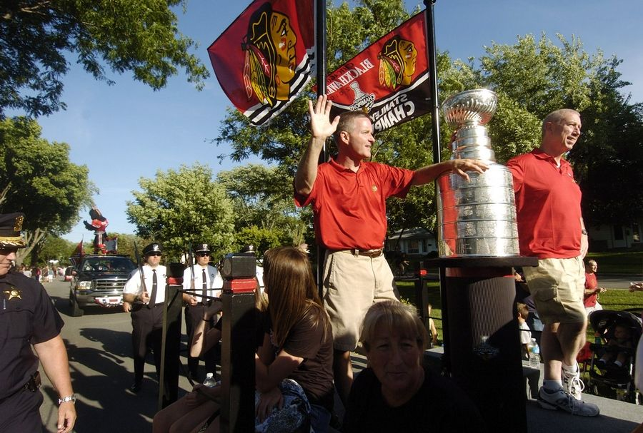 Blackhawks President and CEO John McDonough, right, and Elk Grove Village Mayor Craig Johnson ride with the Stanley Cup during Elk Grove's Hometown Parade in 2010. Johnson announced Tuesday McDonough is bringing the cup back to Elk Grove Village Aug. 29.