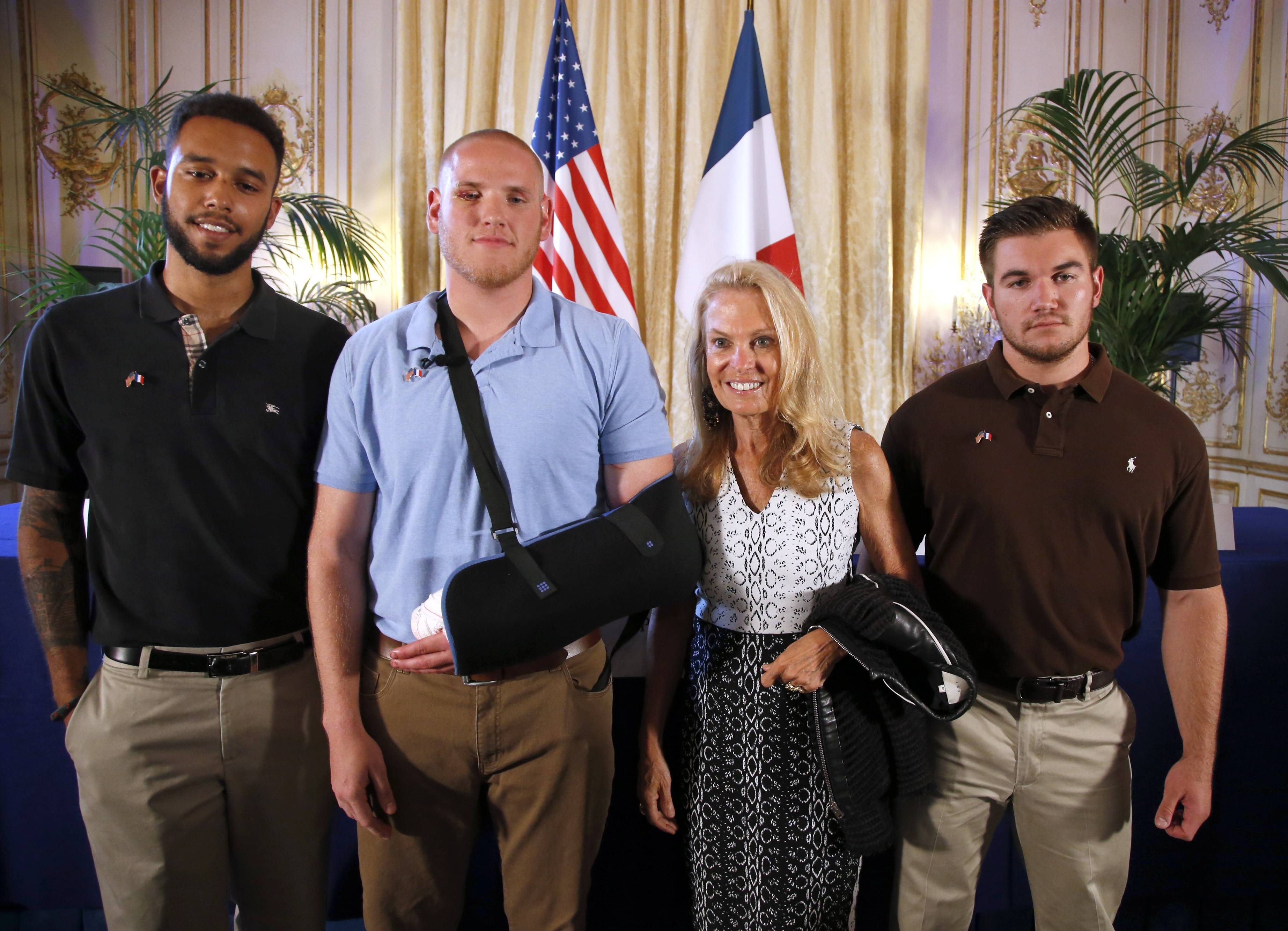 Anthony Sadler, a senior at Sacramento University in California, left, U.S. National Guardsman from Roseburg, Oregon, Alek Skarlatos, right, and U.S. Airman Spencer Stone, second from left, pose for photographers with Jane D. Hartley, U.S. Ambassador to France, before a news conference held at the U.S. Ambassador's residence in Paris, France, Sunday, Aug. 23, 2015. Sadler, Skarlatos and Stone helped foil a potentially deadly attack when they subdued a man armed with an assault rifle and other weapons on board a high-speed train bound for Paris two days ago. The man was known to intelligence services in three countries and had ties to radical Islam, authorities said Sunday. (AP Photo/Francois Mori)