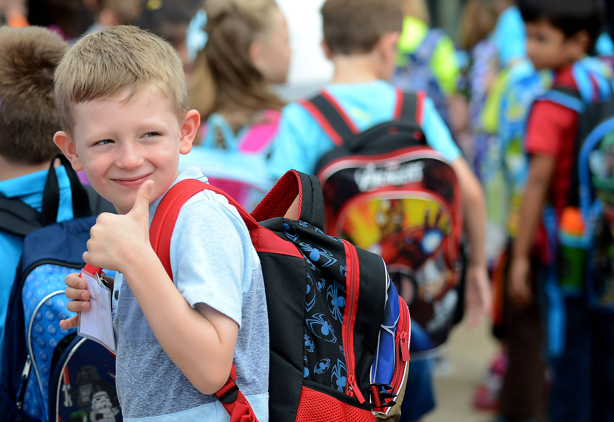 Jack Atkins gives a quick look back and thumbs up to his parents before filing in for his first day of kindergarten at Prairie View Elementary School in Elgin Wednesday.