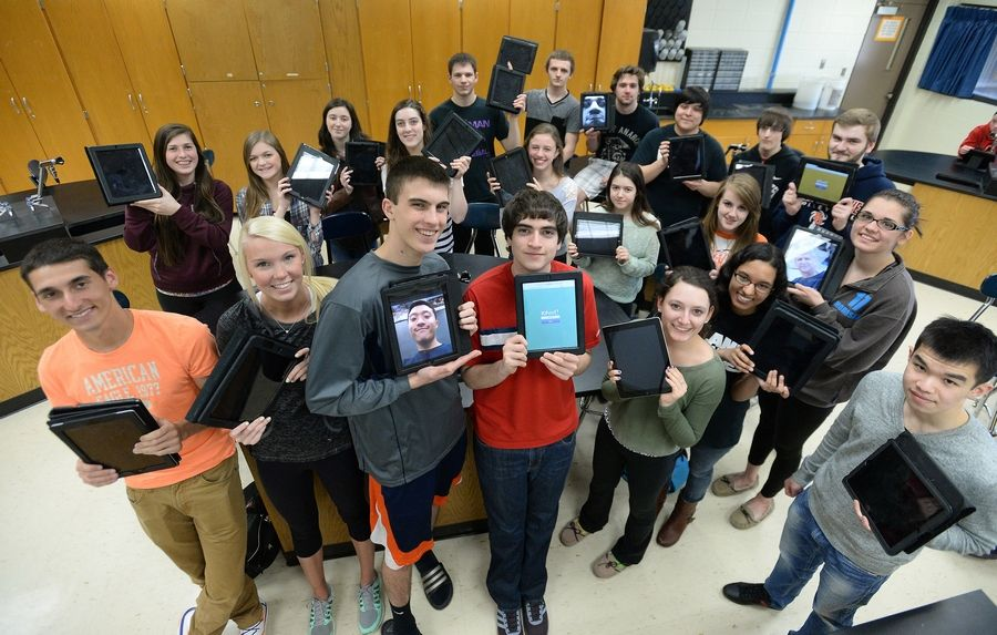 Buffalo Grove High School teacher Tim Kosiek's students show the iPads they've been using in his classroom, in some cases for as long as three years. When the new school year starts Thursday in Northwest Suburban High School District, each of the district's more than 12,000 students will receive an iPad.