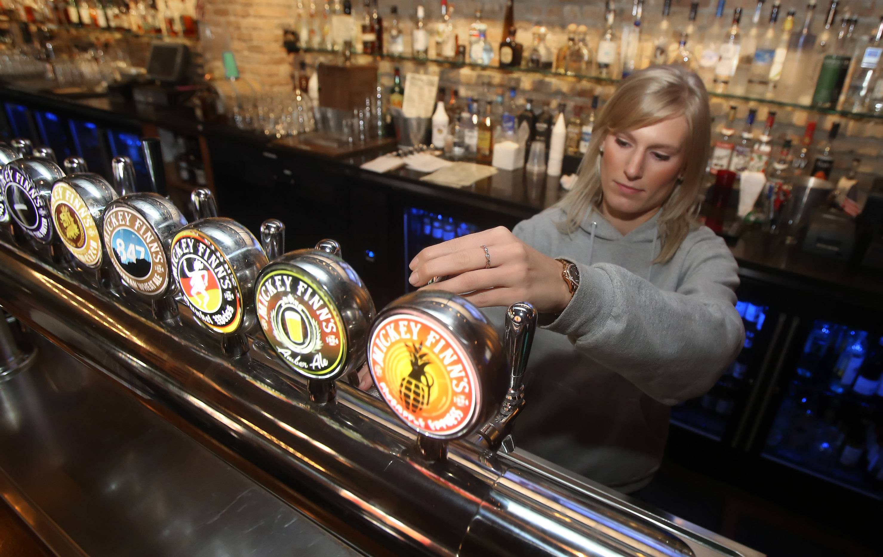 Bartender Miranda Sherwin pours a beer at Mickey Finn's in Libertyville.