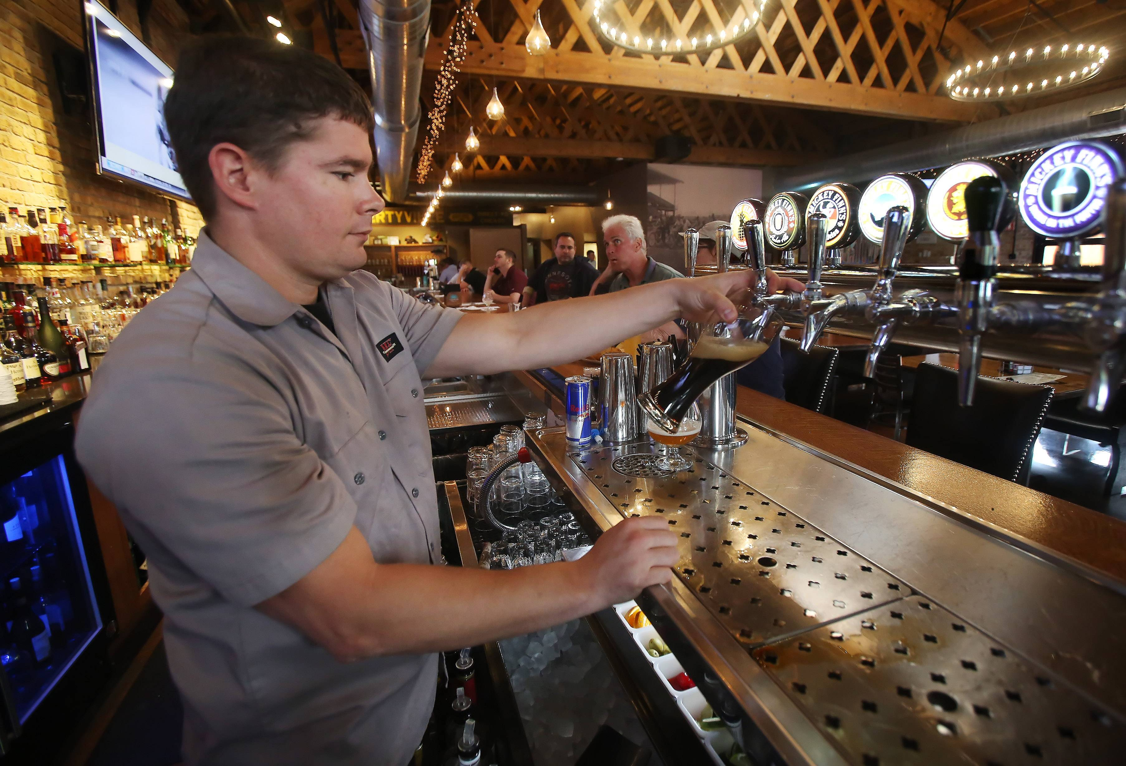 Bar manager Kevin Baird pours a beer at Mickey Finn's in Libertyville.