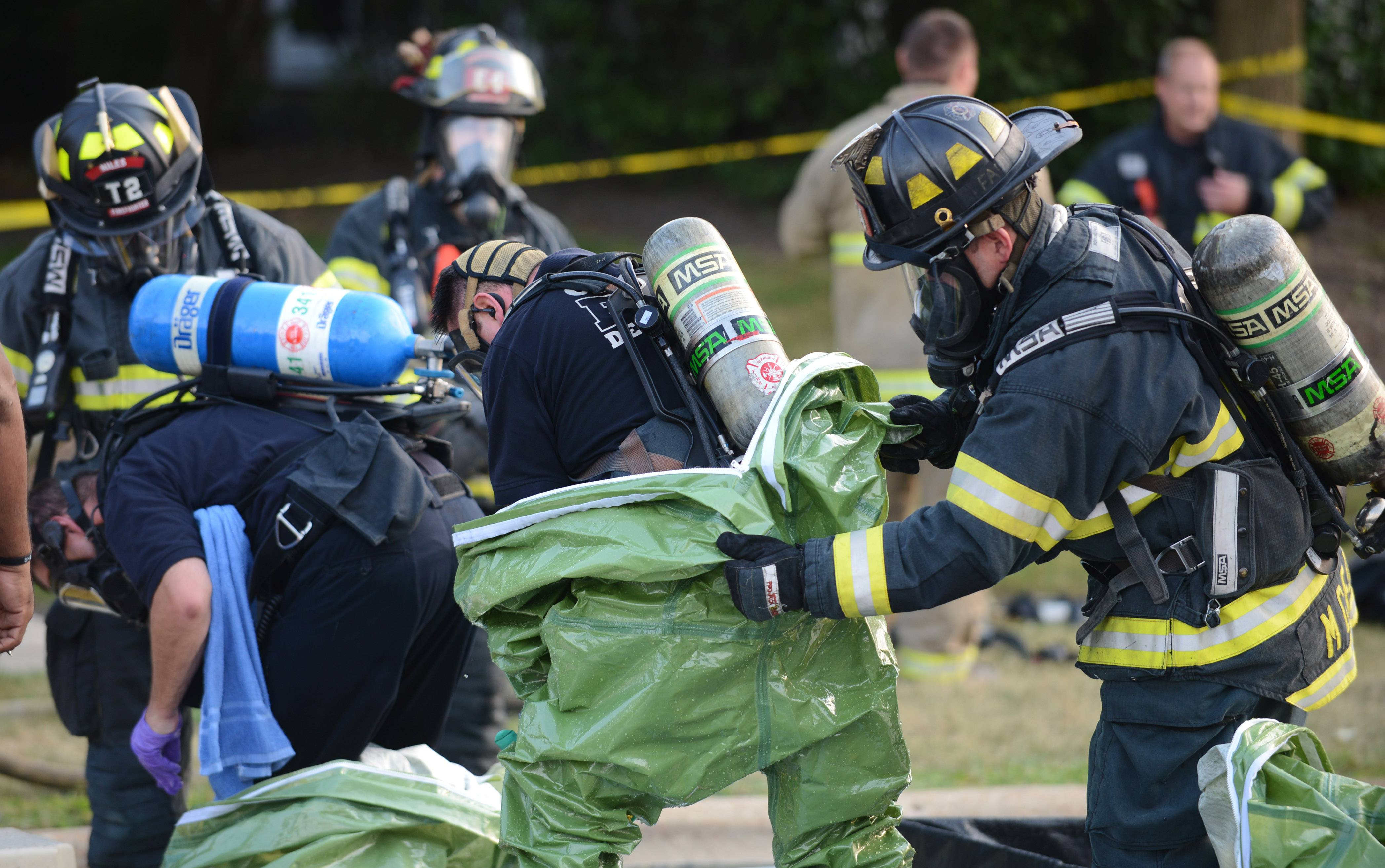 Firefighters remove their protective suits after responding to a hazardous materials situation on the 9400 block of Harrison Street Thursday in an unincorporated area near Des Plaines. Two men were found dead in the home, and a woman living there was listed in critical condition late Thursday.