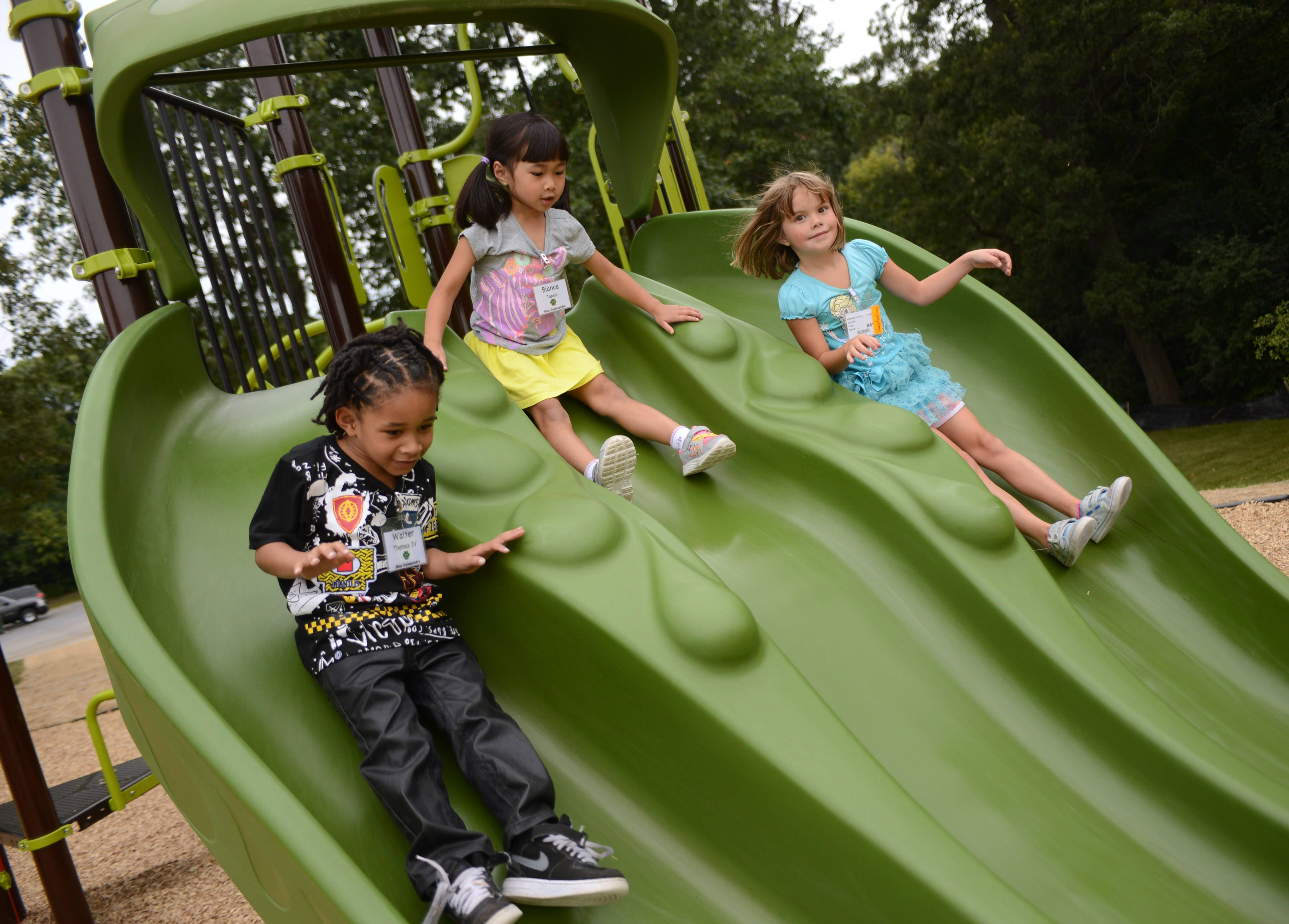 Woodland Primary School kindergarten students Walter Thomas, left, Bianca Tapnio and Hope Gaston play on the school's new playground Friday during recess in Gages Lake.