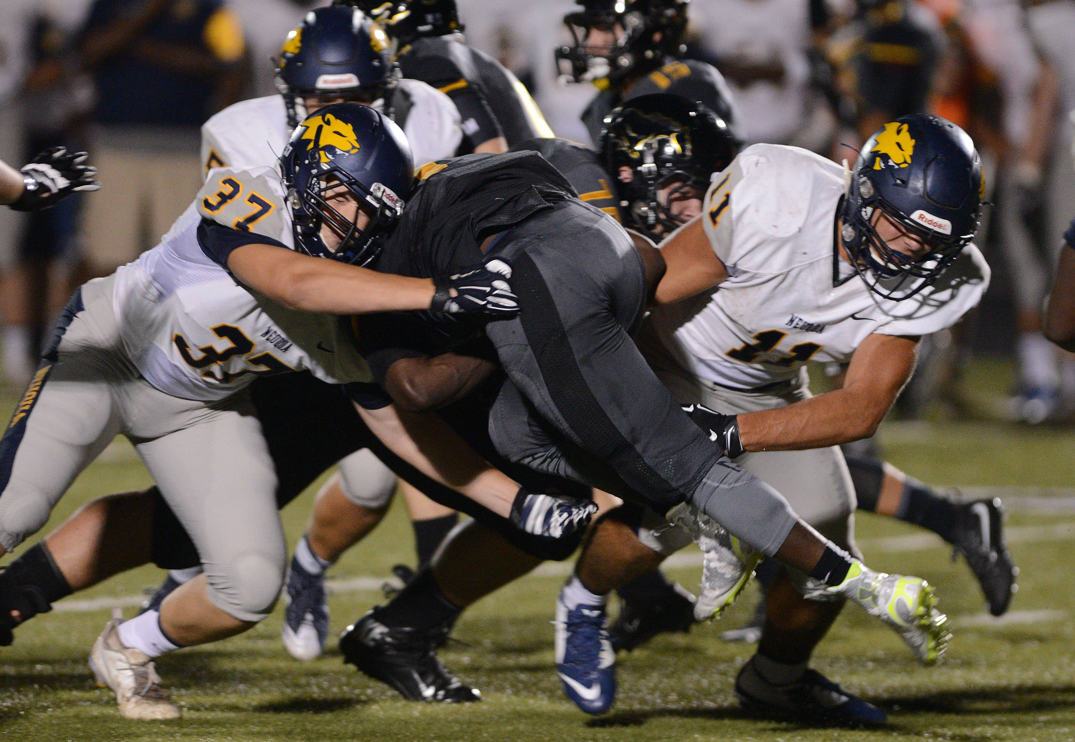 Casey Larson,left, and Jon Rhattigan of Neuqua Valley pull down a Metea Valley player.