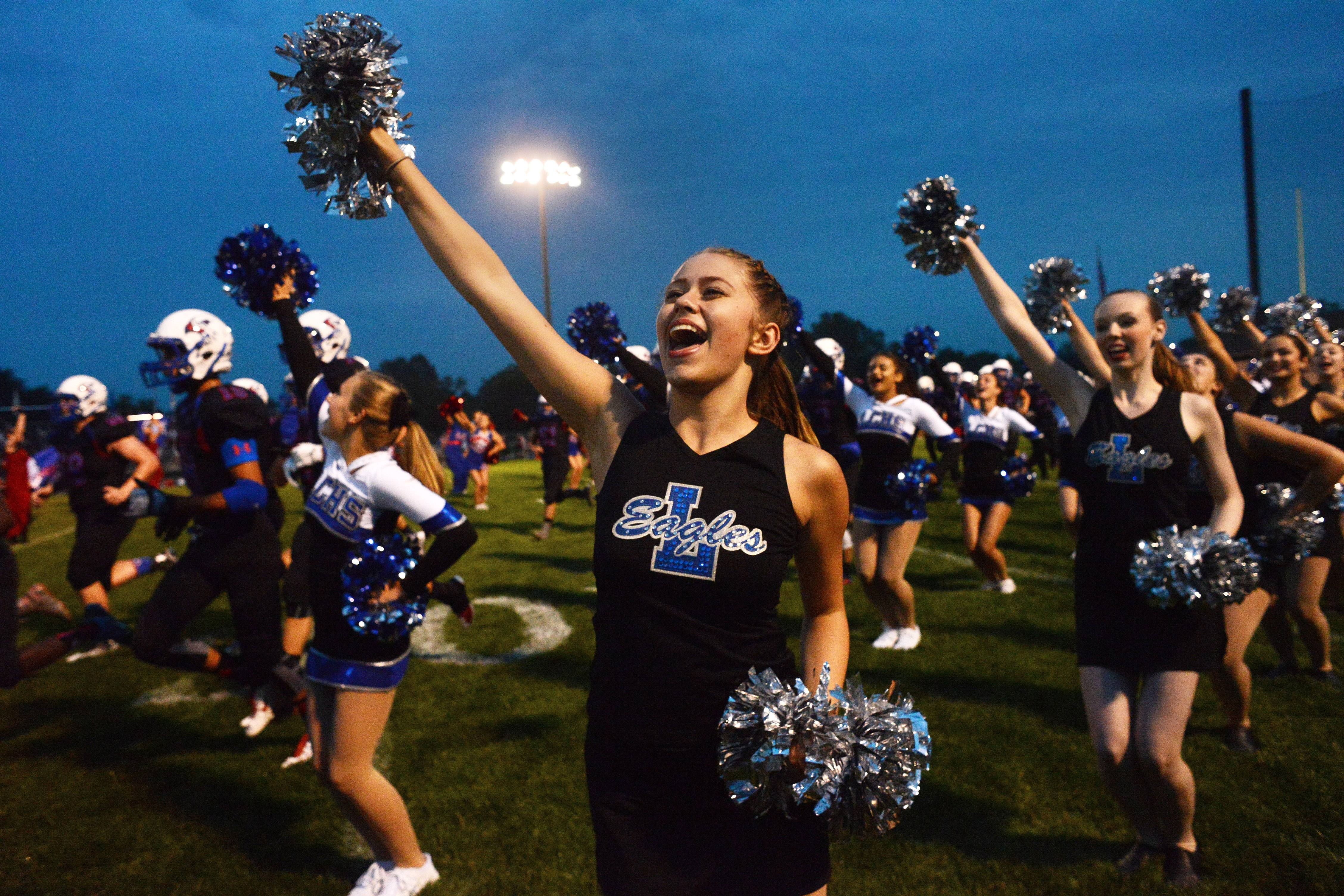 Sophomore Mya Pfeifer of the junior varsity pom squad cheers as the football team runs onto the field during Friday's season opener in Lake Villa.