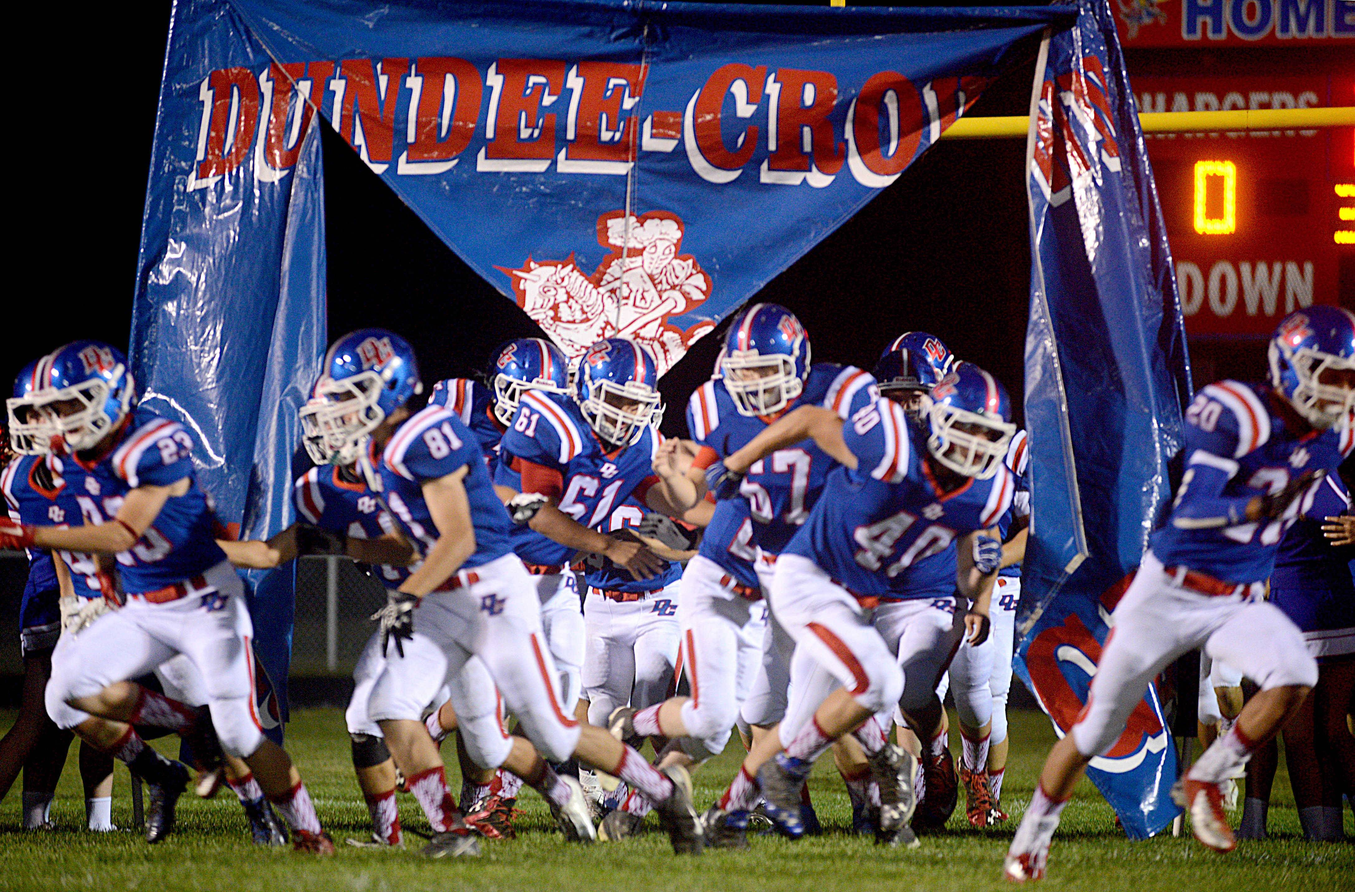 The Chargers of Dundee-Crown rip through the barrier to begin their 2015 campaign against Elgin's Maroons at Carpentersville Friday night.