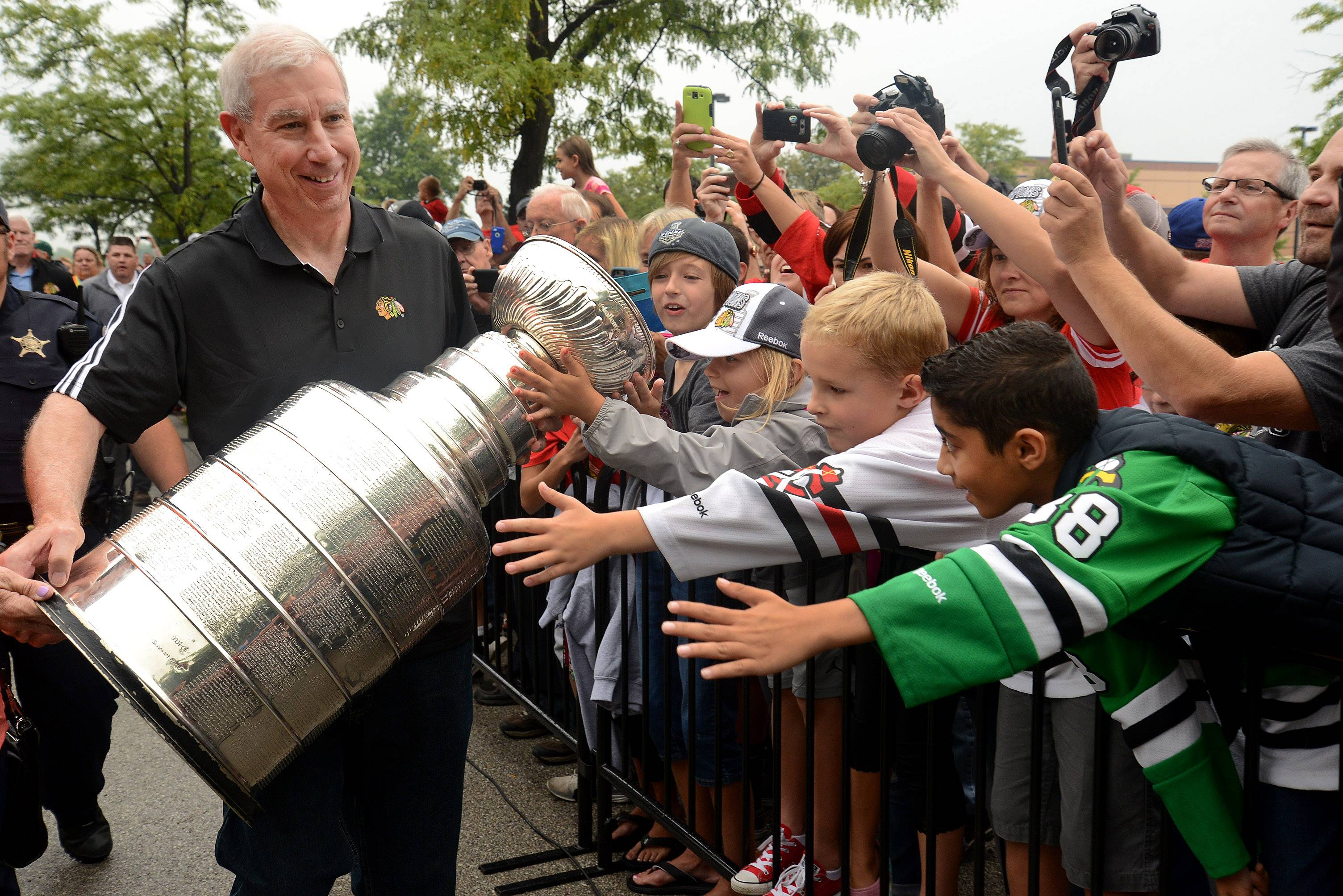 Blackhawks team President and CEO John McDonough brings the Stanley Cup back to Elk Grove Village during a rally Saturday morning.